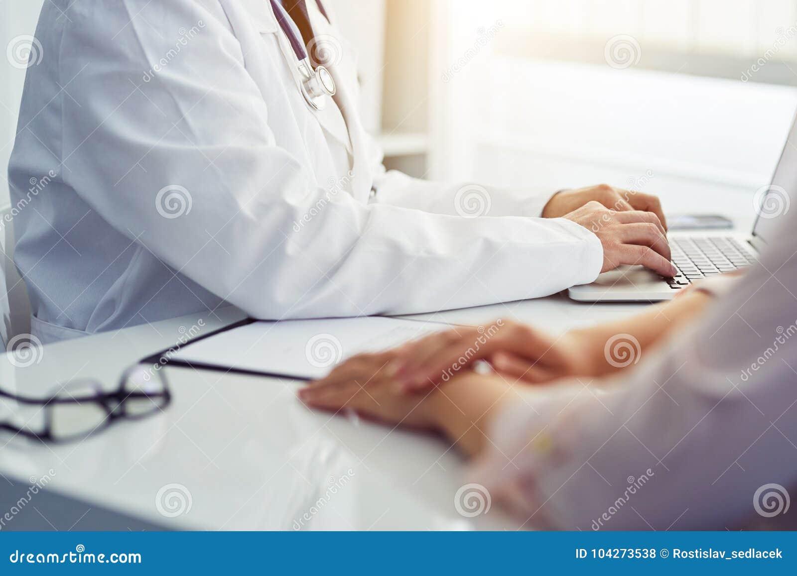 Manlig doktor med tålmodigt sammanträde på skrivbordet och handstil på bärbara datorn