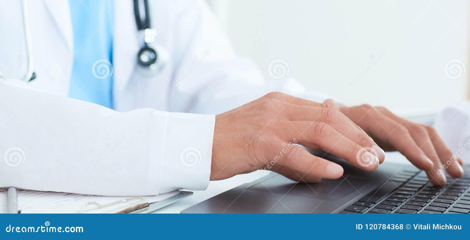 Manlig doktor, medicinare eller kirurg som använder bärbara datorn under konferensen Vård- kontroll med service för digitalt syst
