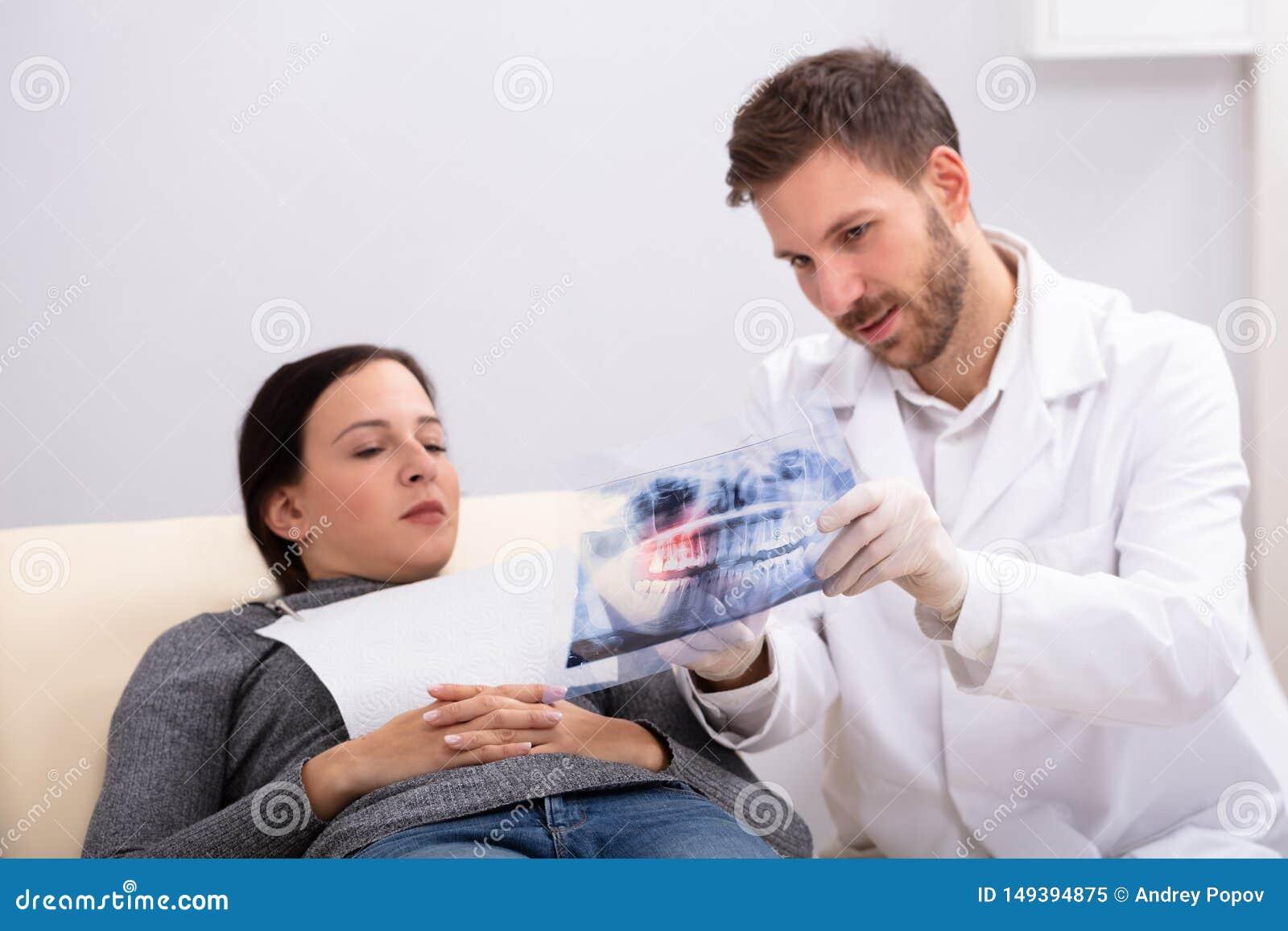 Manlig doktor som f?rklarar r?ntgenstr?len till patienten