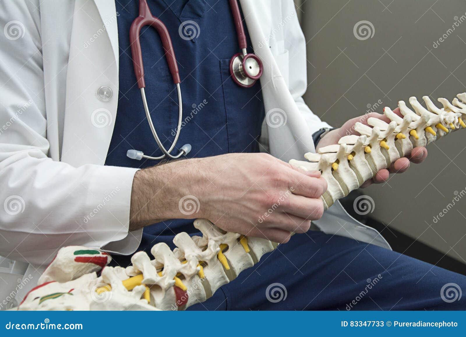 Manlig doktor som rymmer en rygg och talar till patienten