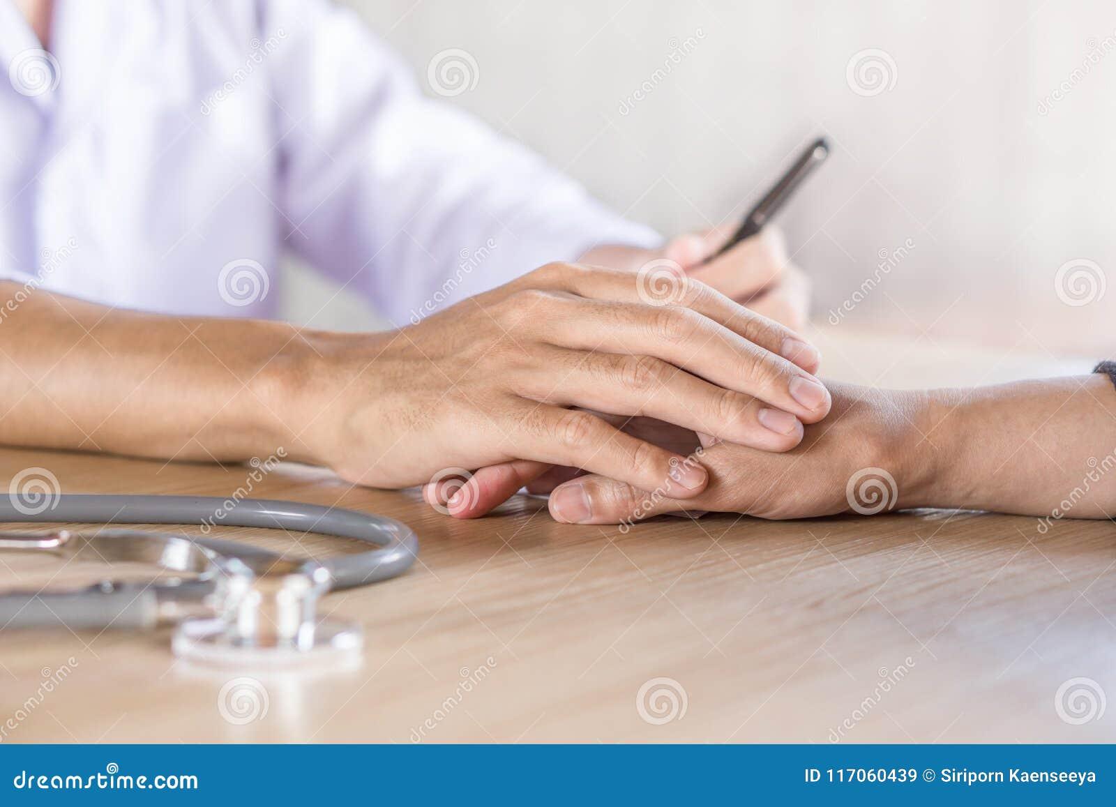 Manlig doktorsinnehavhand och tröstapatient i ett sjukhus