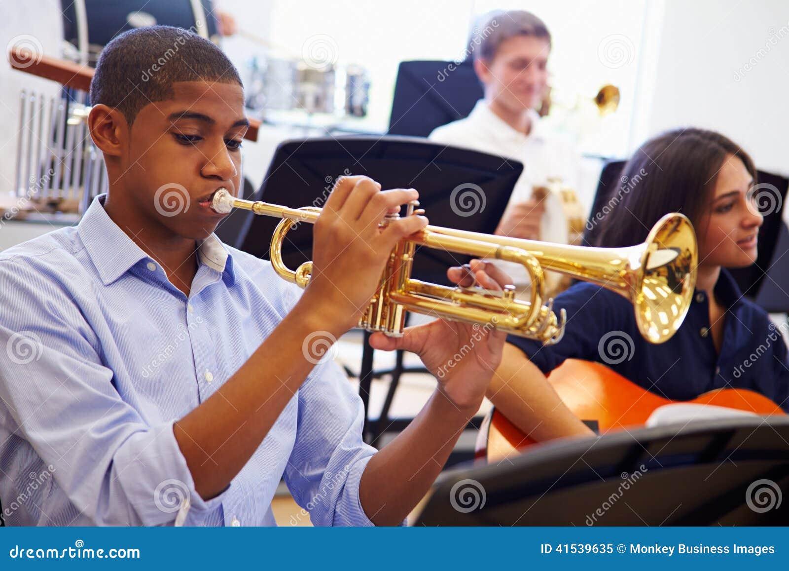 Manlig elev som spelar trumpeten i högstadiumorkester