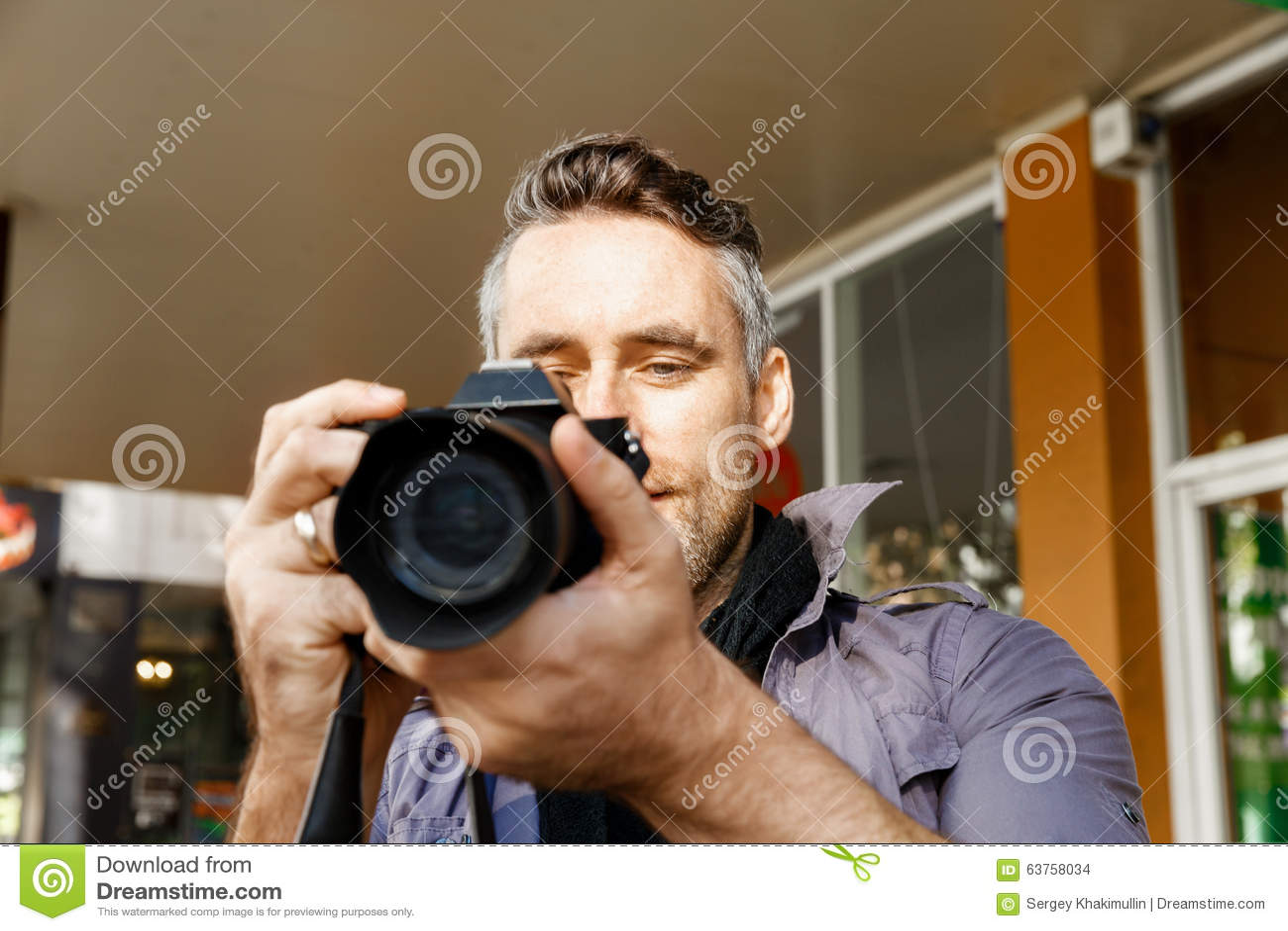 Manlig fotograf som tar bilden