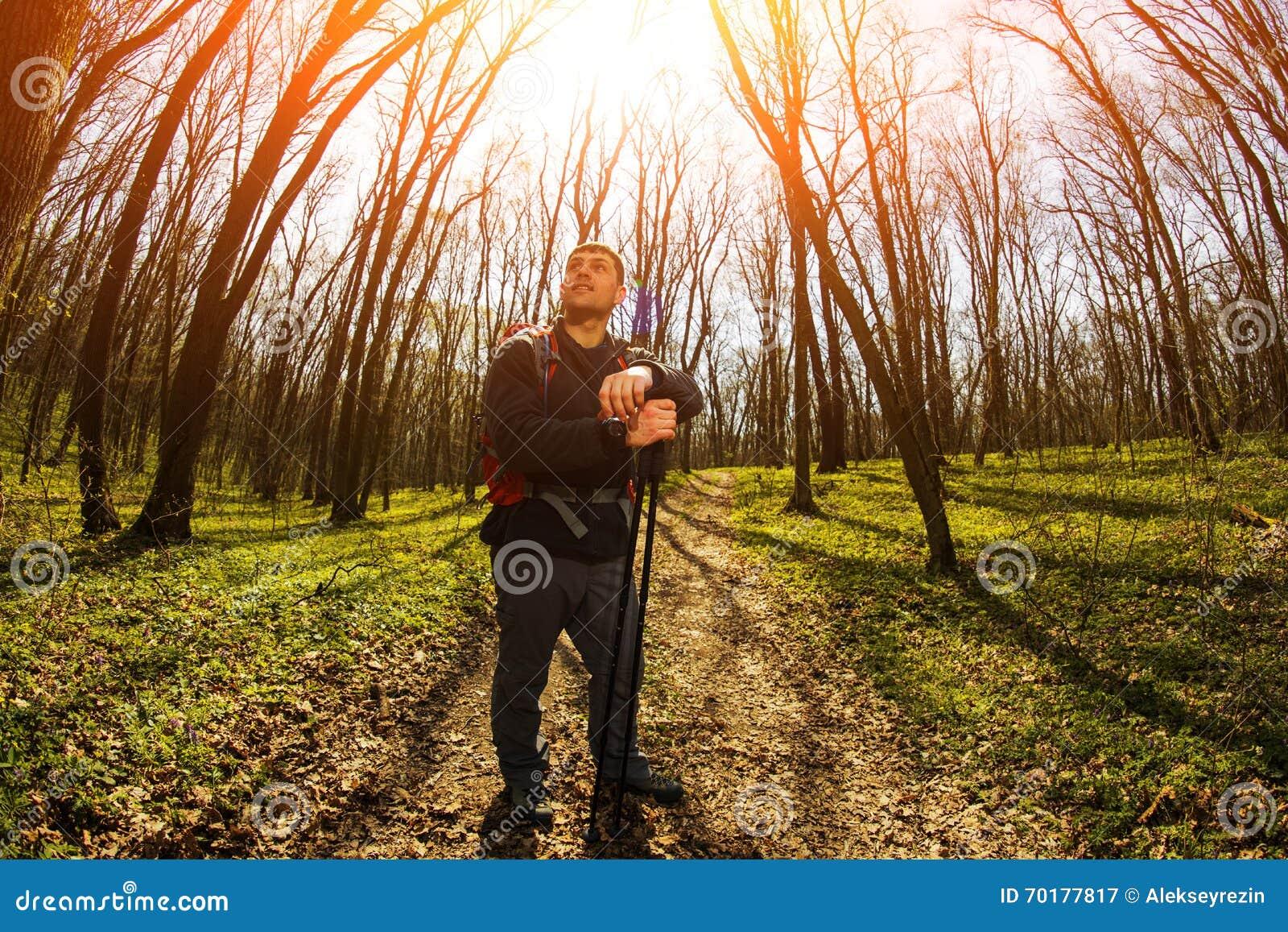Manlig fotvandrare som ser till sidan som går i skog
