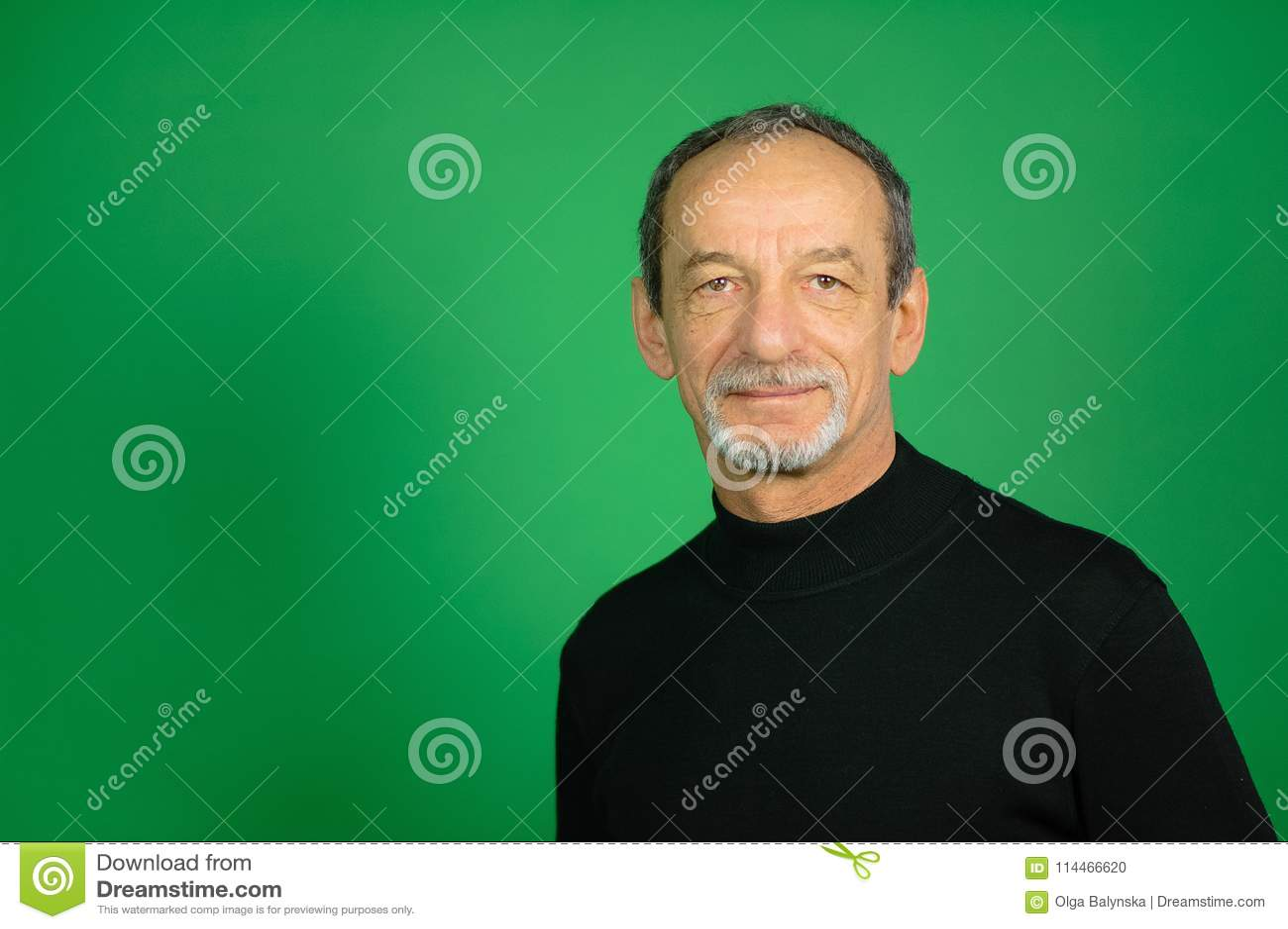 Manlig framsida av den höga mannen med detklippte skägget och Gray Hair på en grön bakgrund i studio