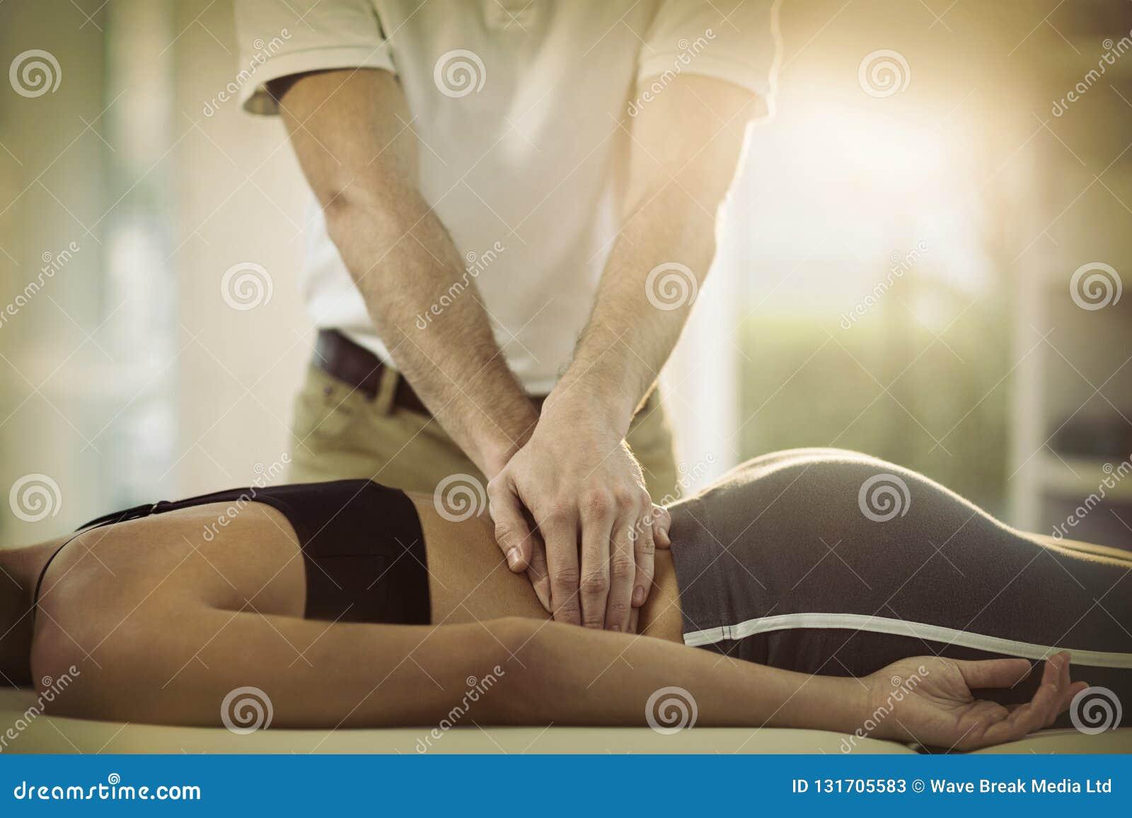 Manlig fysioterapeut som tillbaka ger massage till den kvinnliga patienten