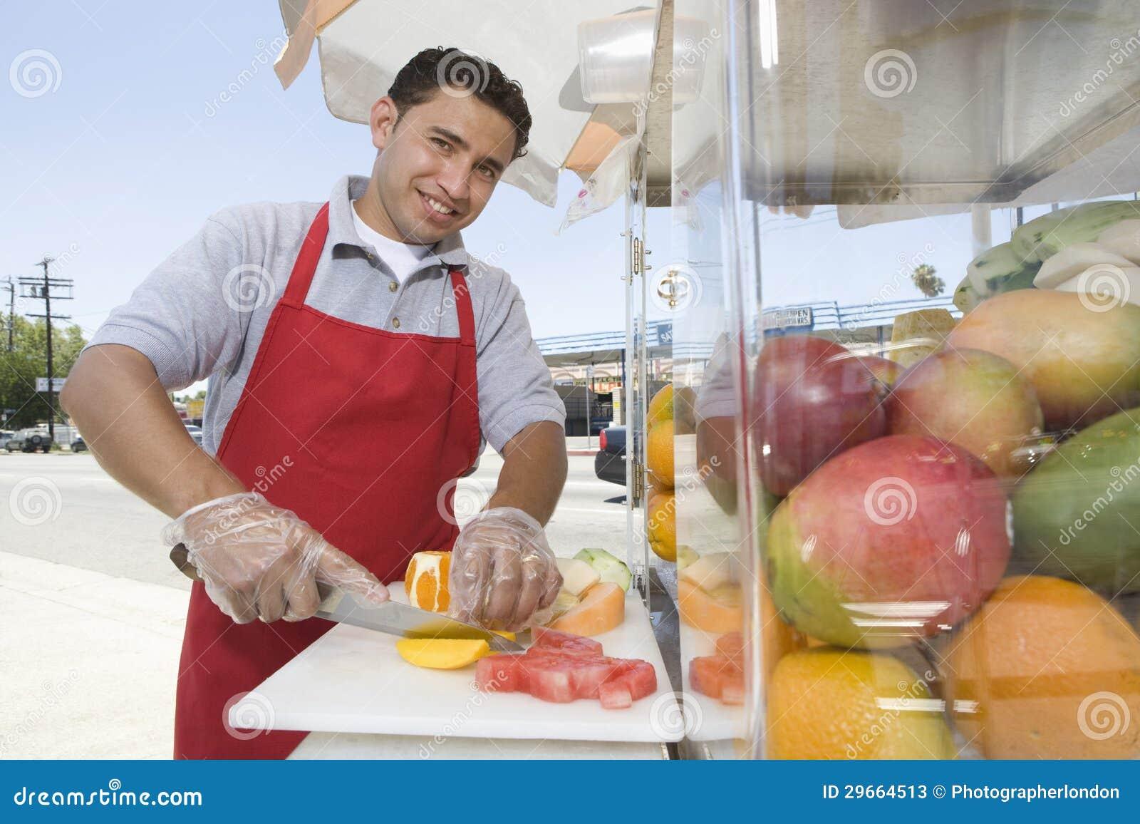 Manlig gatuförsäljare Chopping Fruits