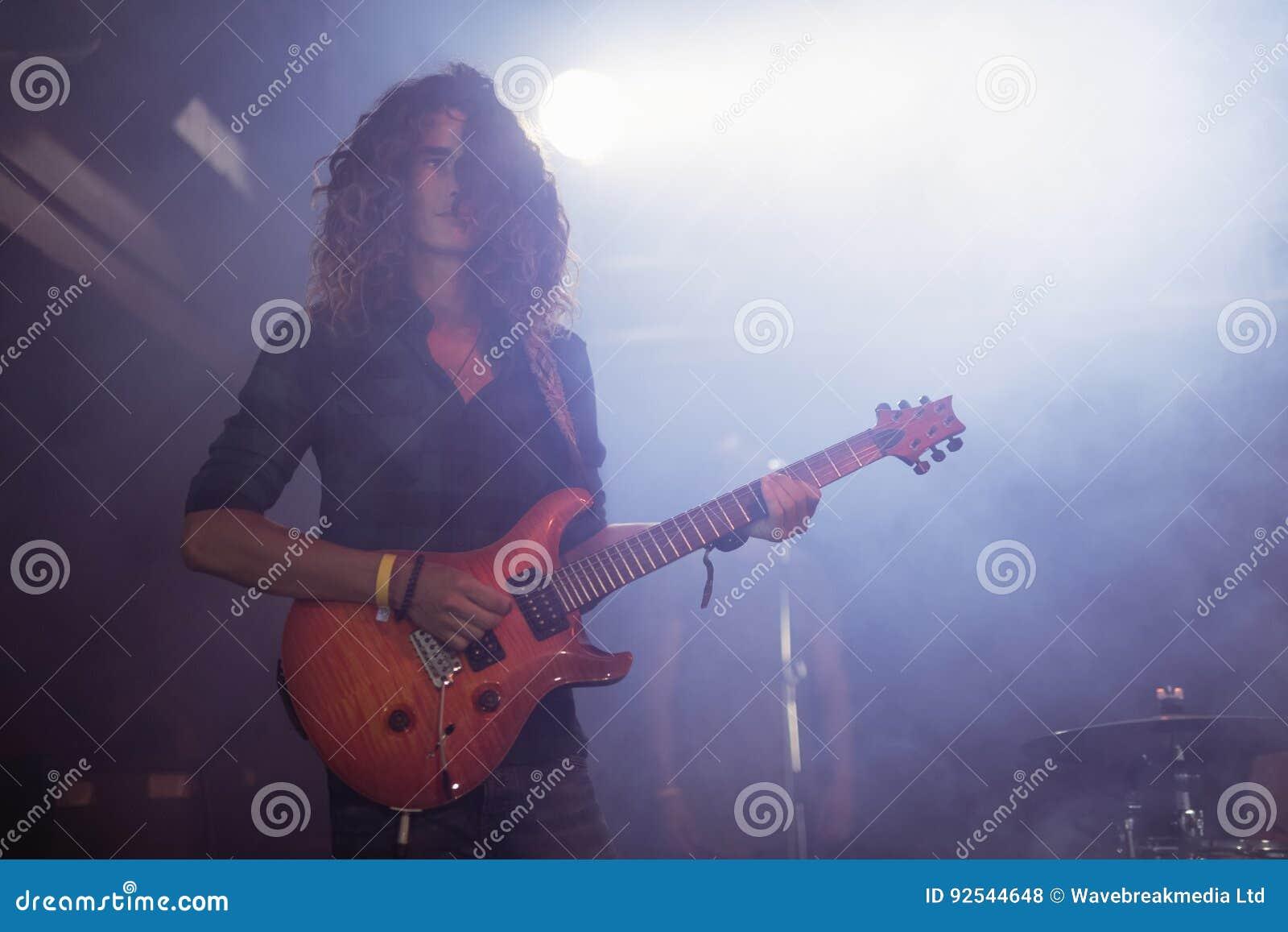 Manlig gitarrist som utför med lockigt hår på nattklubben