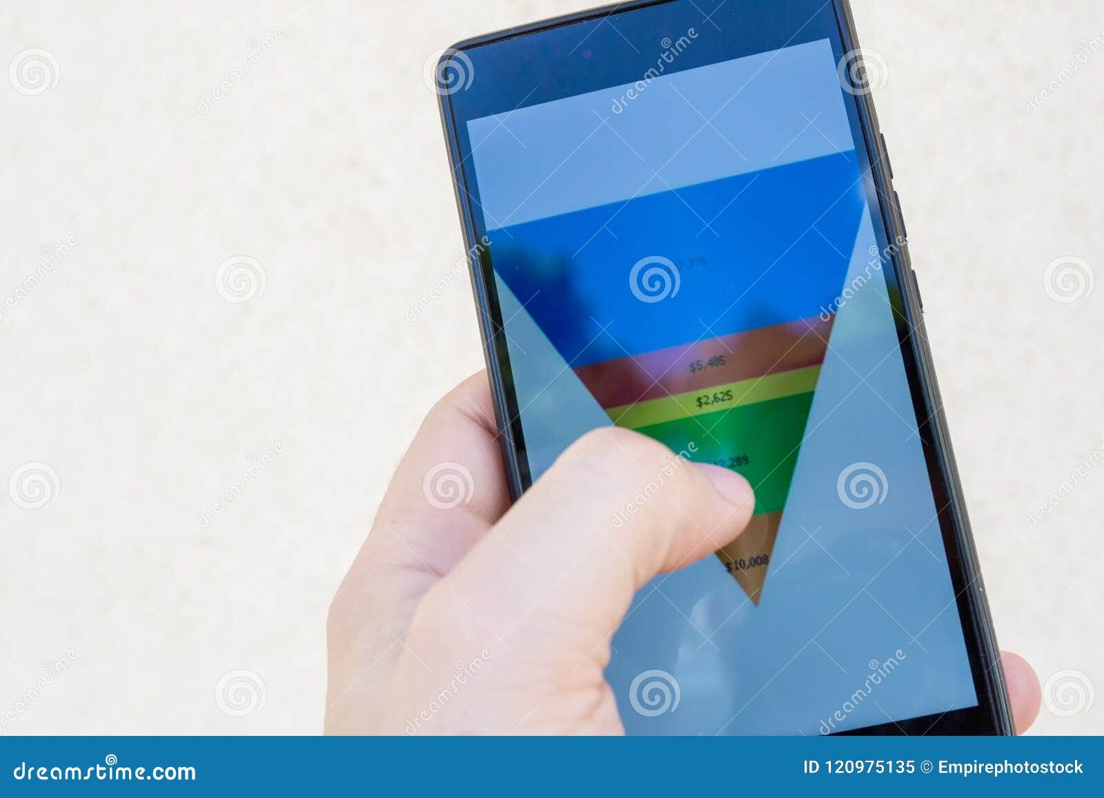 Manlig hand som rymmer en smart telefon med försäljningstrattdiagrammet