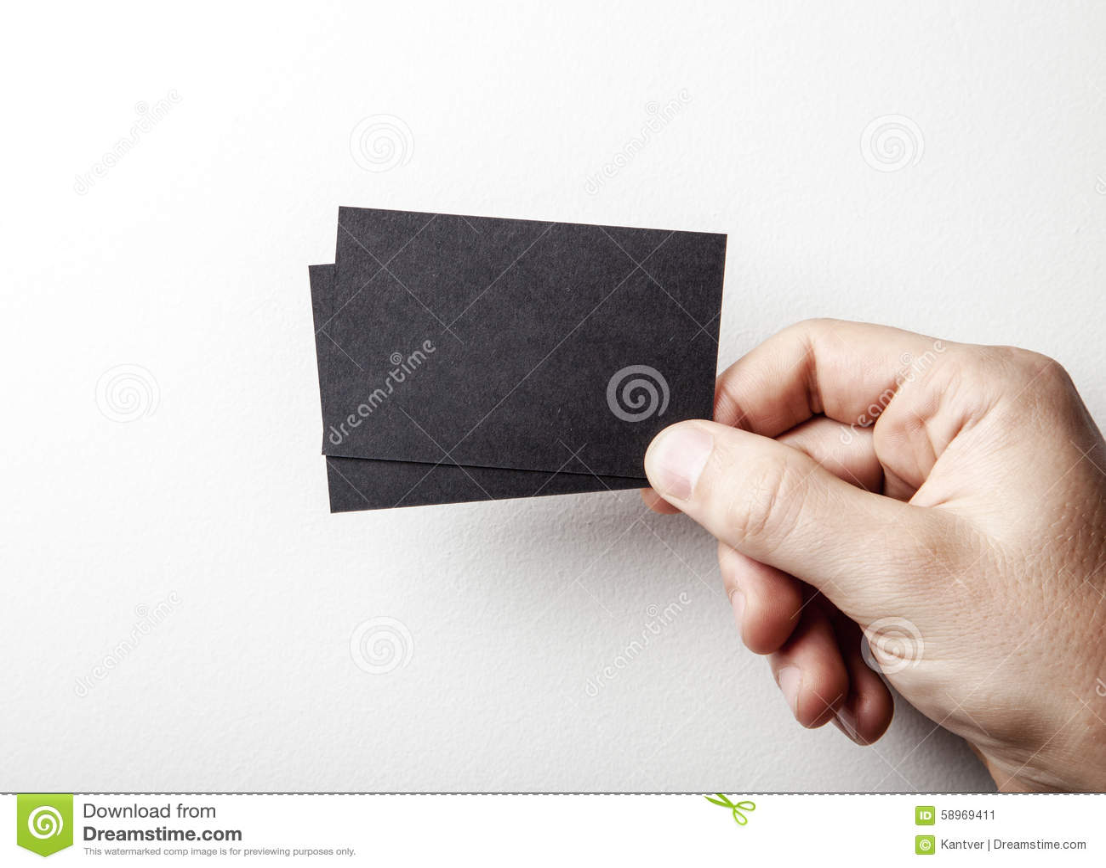 Manlig hand som rymmer två svarta affärskort på
