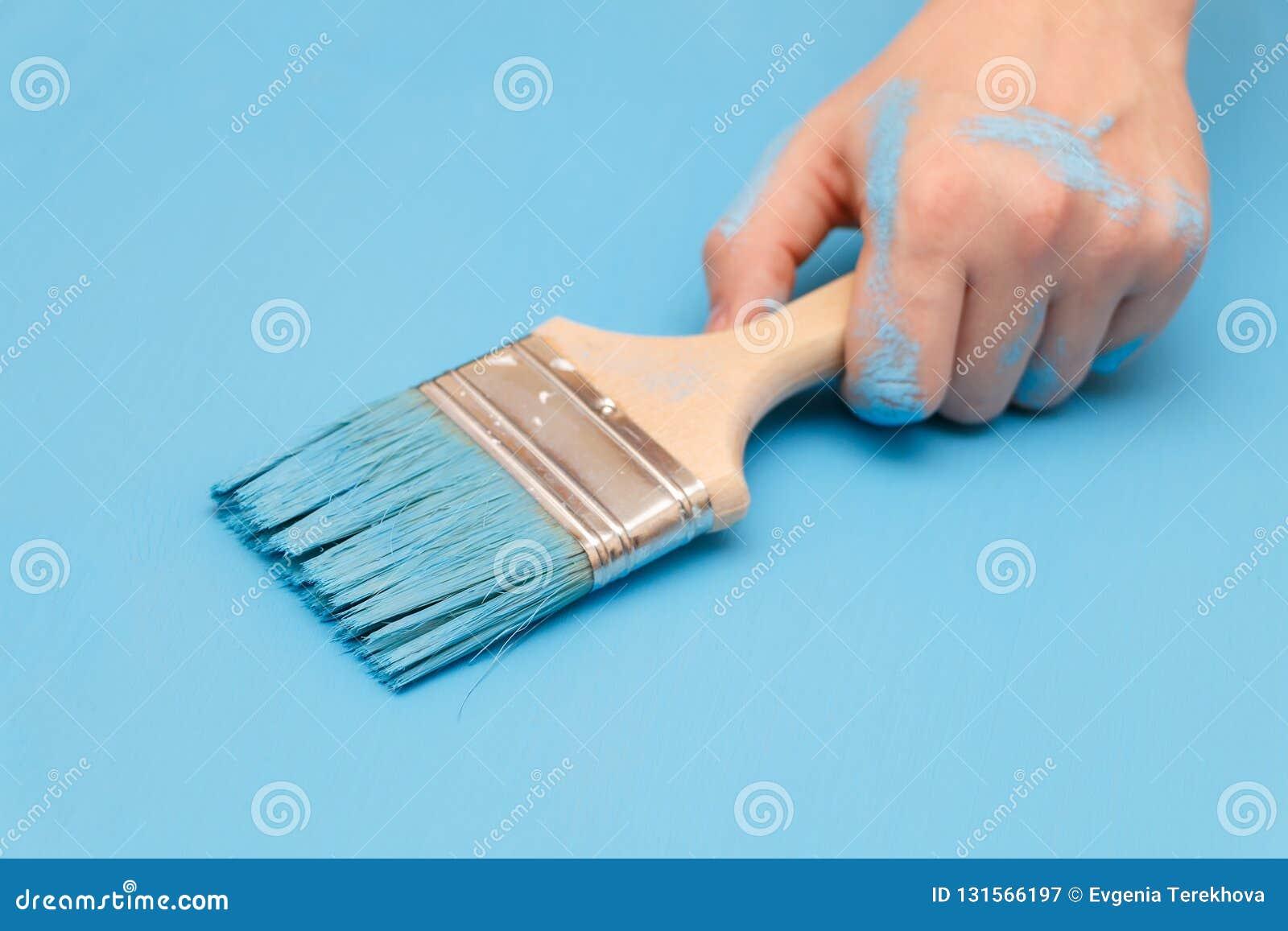 Manlig hand som täckas i målarfärg som rymmer en målarfärgborste på en träbakgrundsyttersida