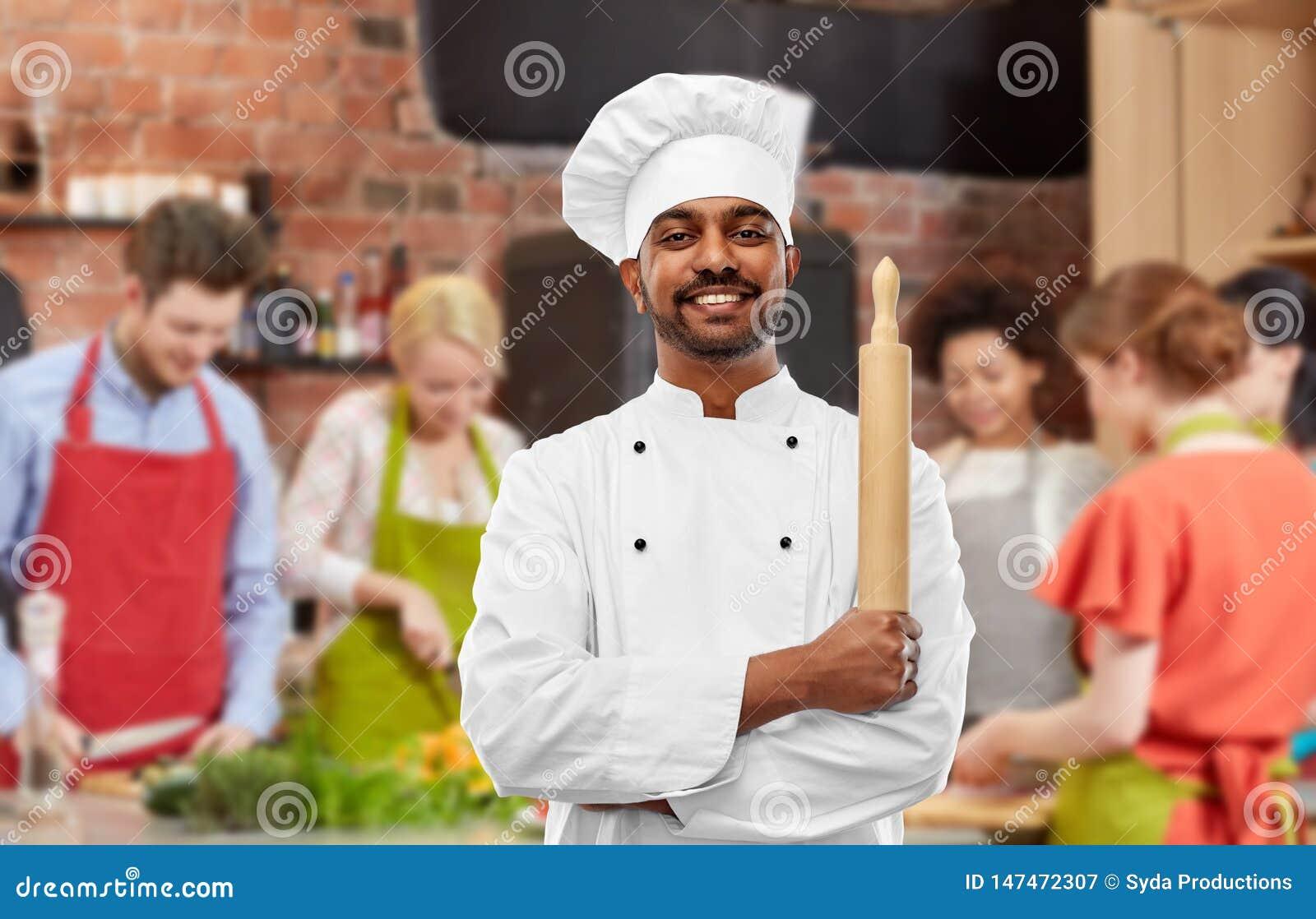 Manlig indisk kock med kavlen på matlagninggrupp