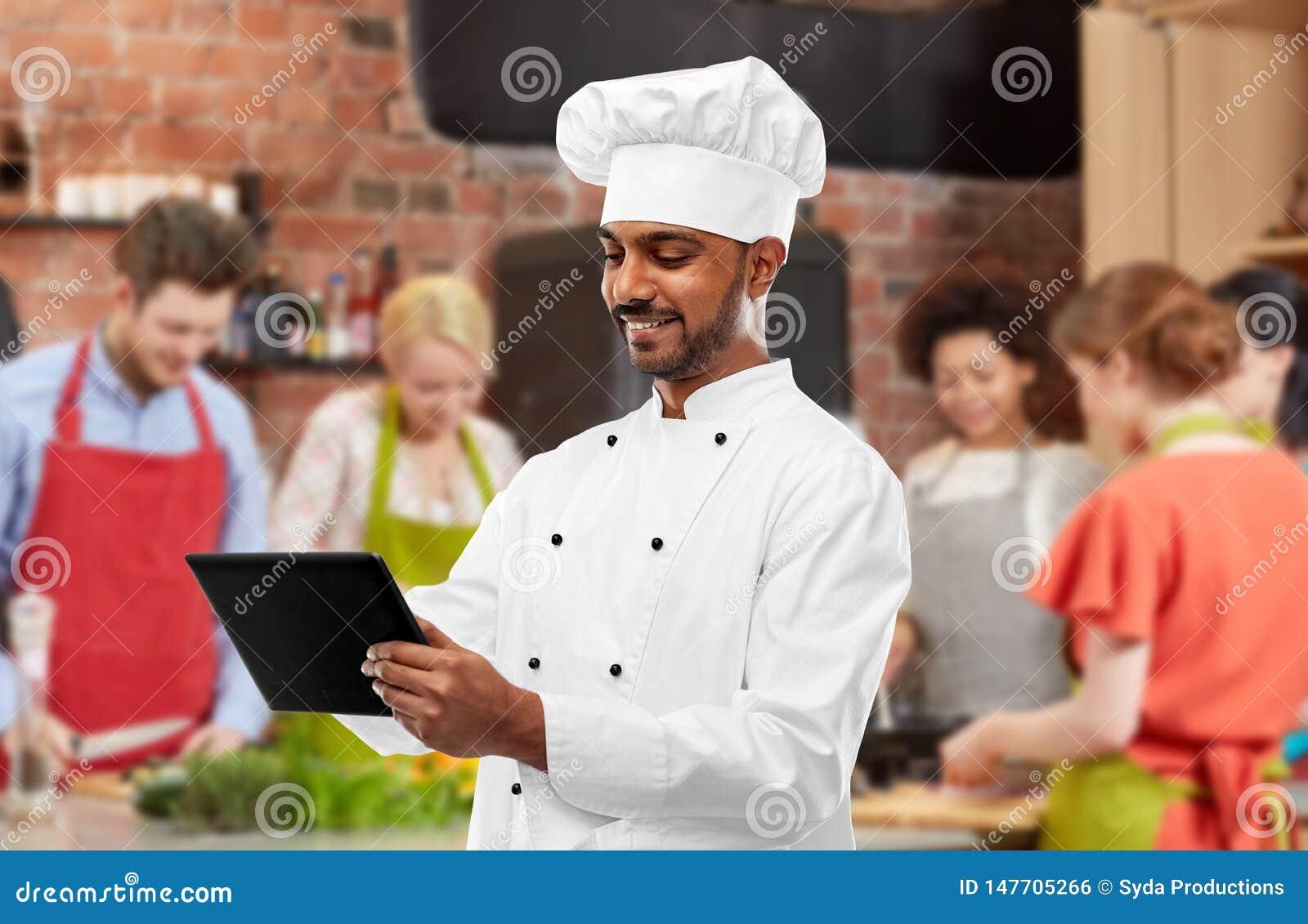 Manlig indisk kock med minnestavlaPC p? matlagninggrupp