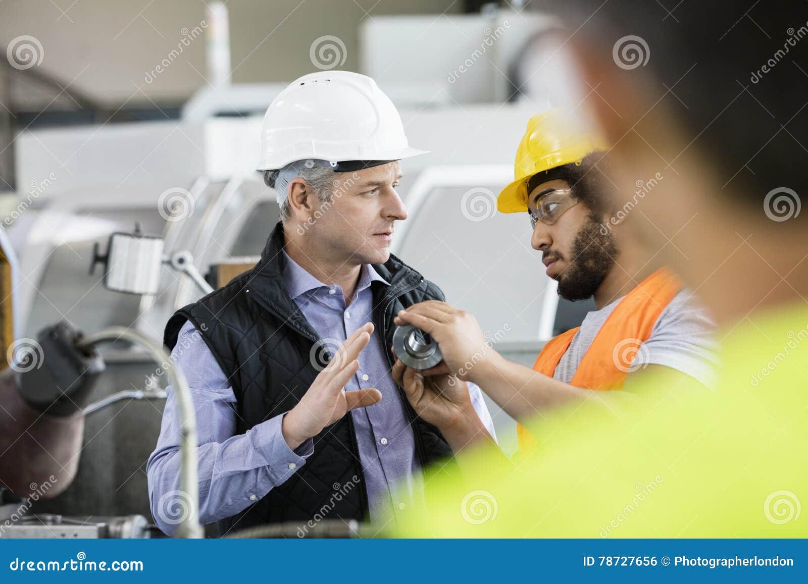 Manlig inspektör som har diskussion med arbetaren i metallbransch