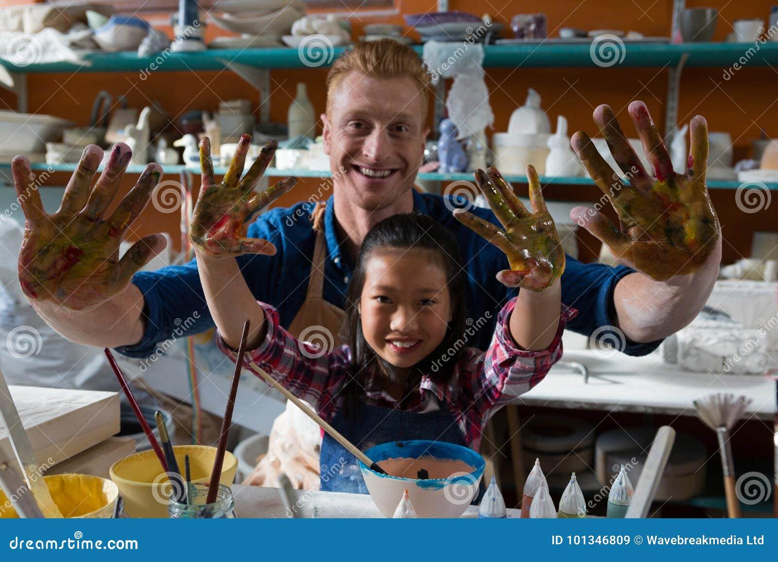 Manlig keramiker och flicka som visar deras målade händer