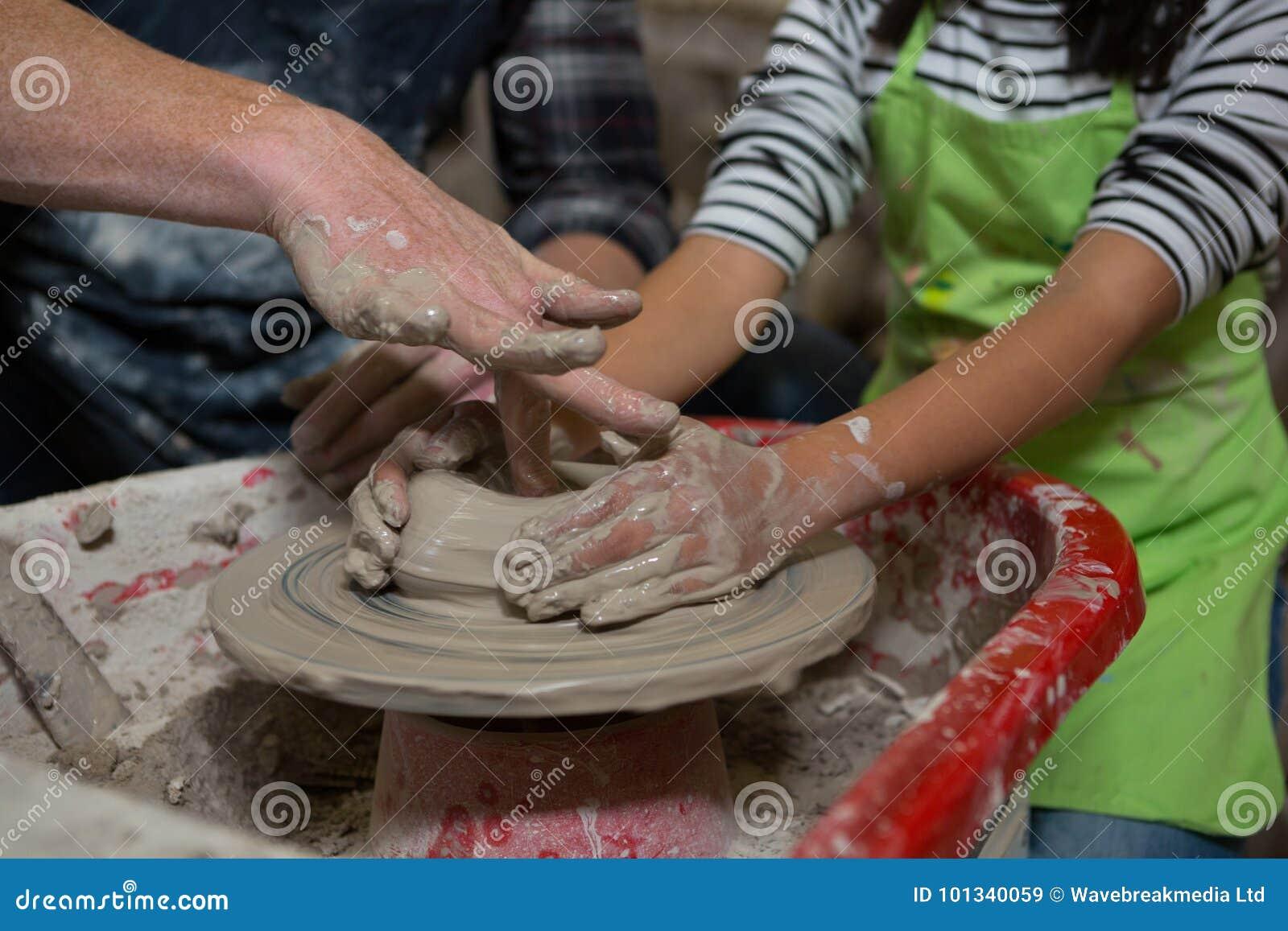 Manlig keramiker som hjälper hans dotter, i framställning av en kruka