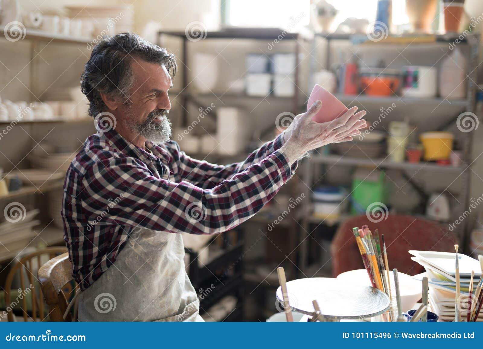 Manlig keramiker som ser den målade bunken