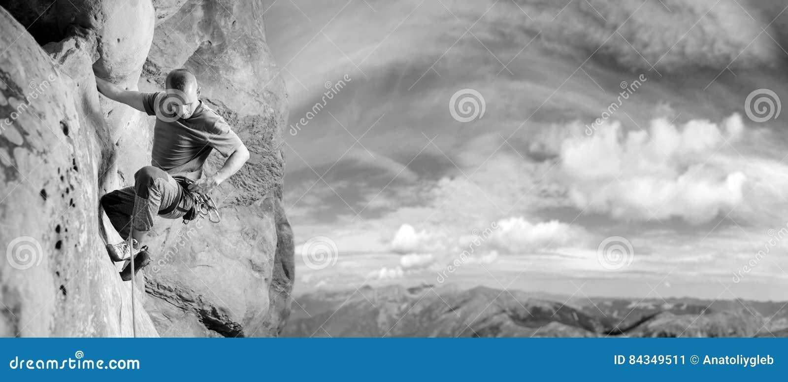 Manlig klättrare som klättrar den stora stenblocket i natur med repet