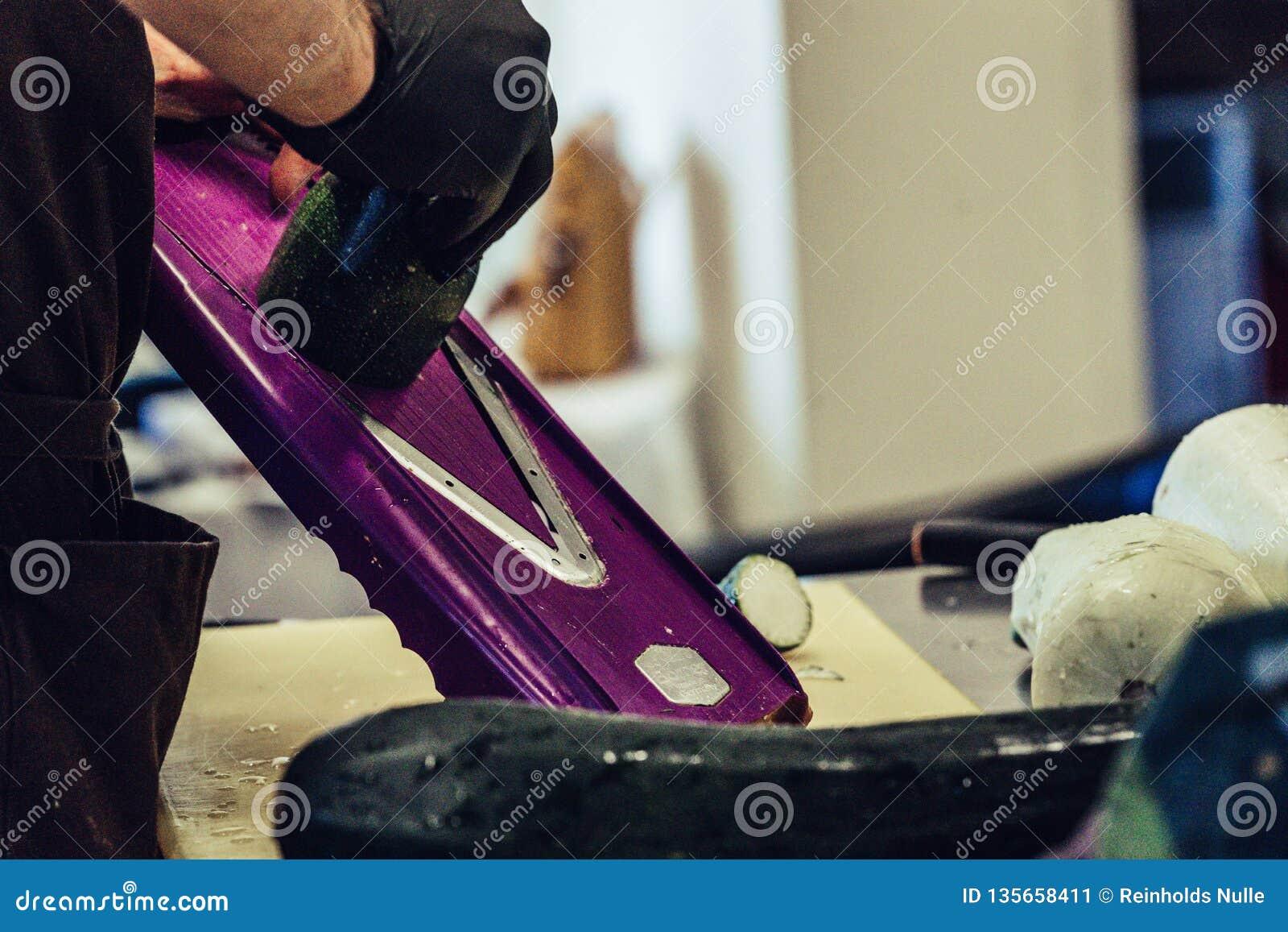 Manlig kock Cutting Eggplant i köket - med handsken på hans hand, begrepp av den hårda funktionsdugliga personen och hygienen i