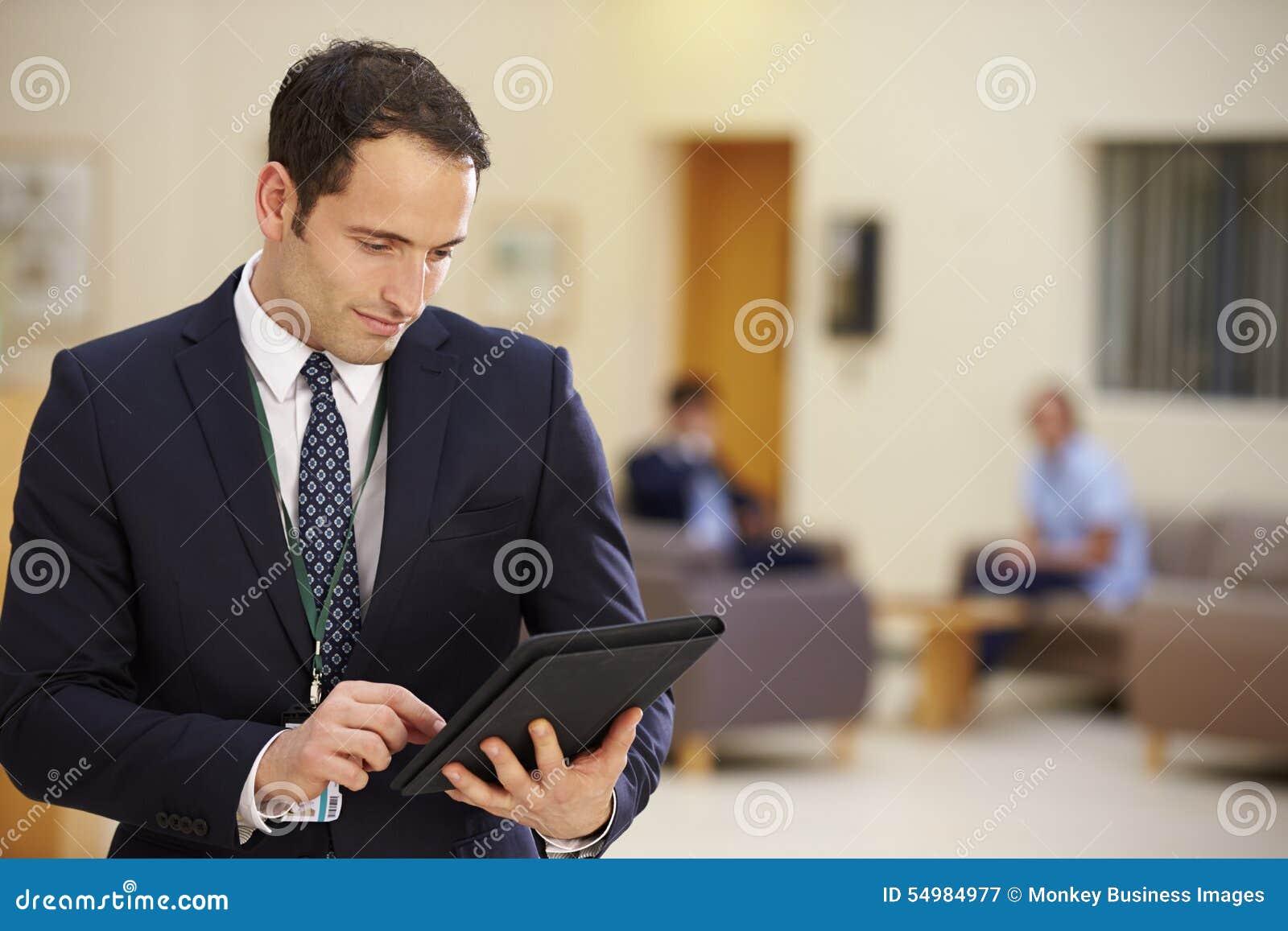 Manlig konsulent Using Digital Tablet i sjukhusmottagande