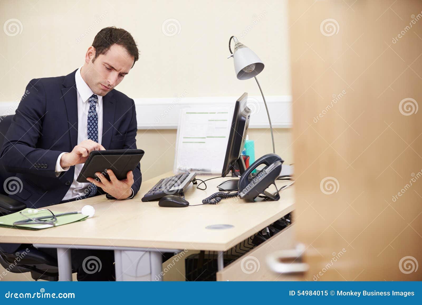 Manlig konsulent Using Digital Tablet på skrivbordet i regeringsställning