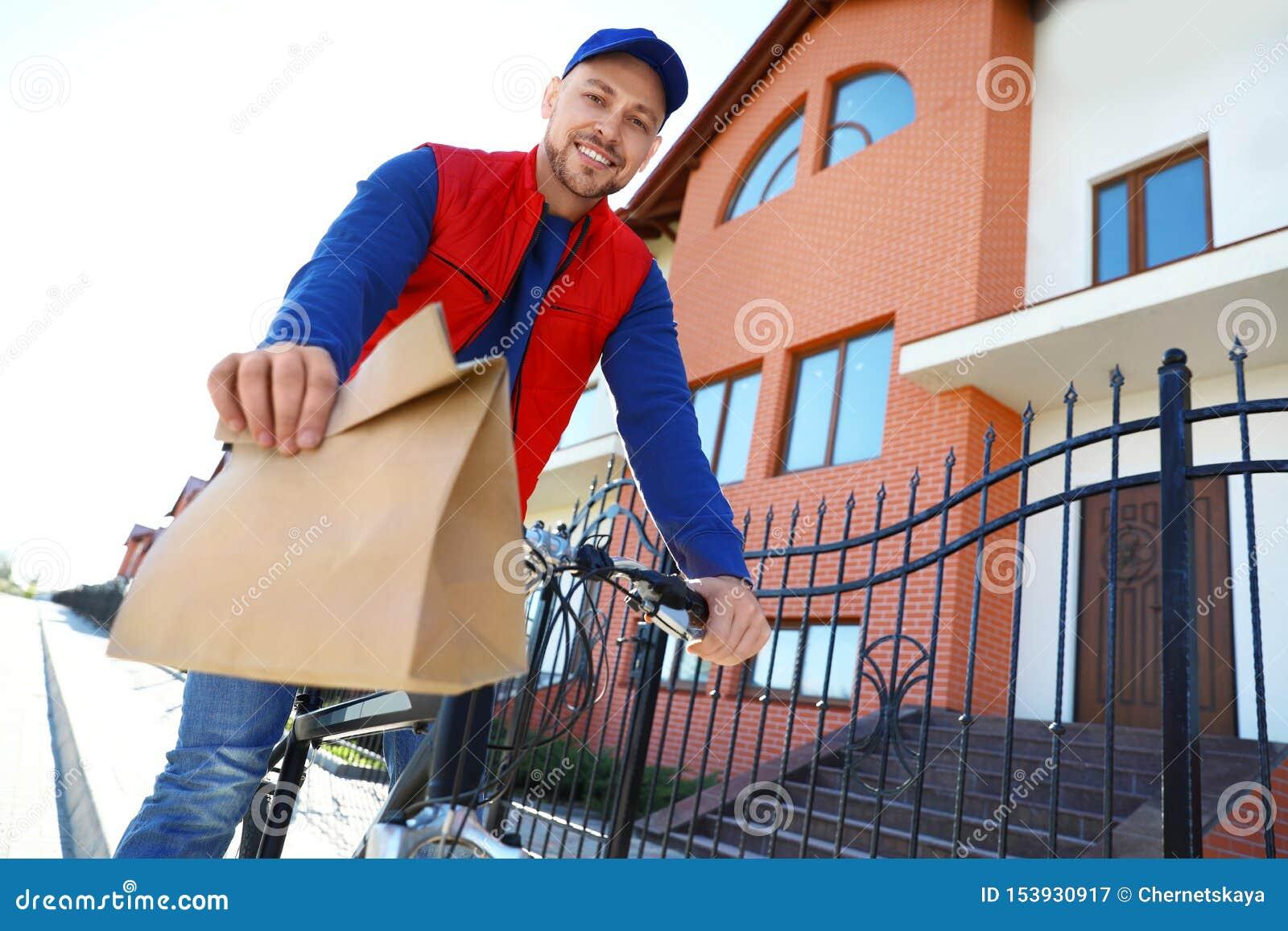 Manlig kurir på cykeln som levererar mat