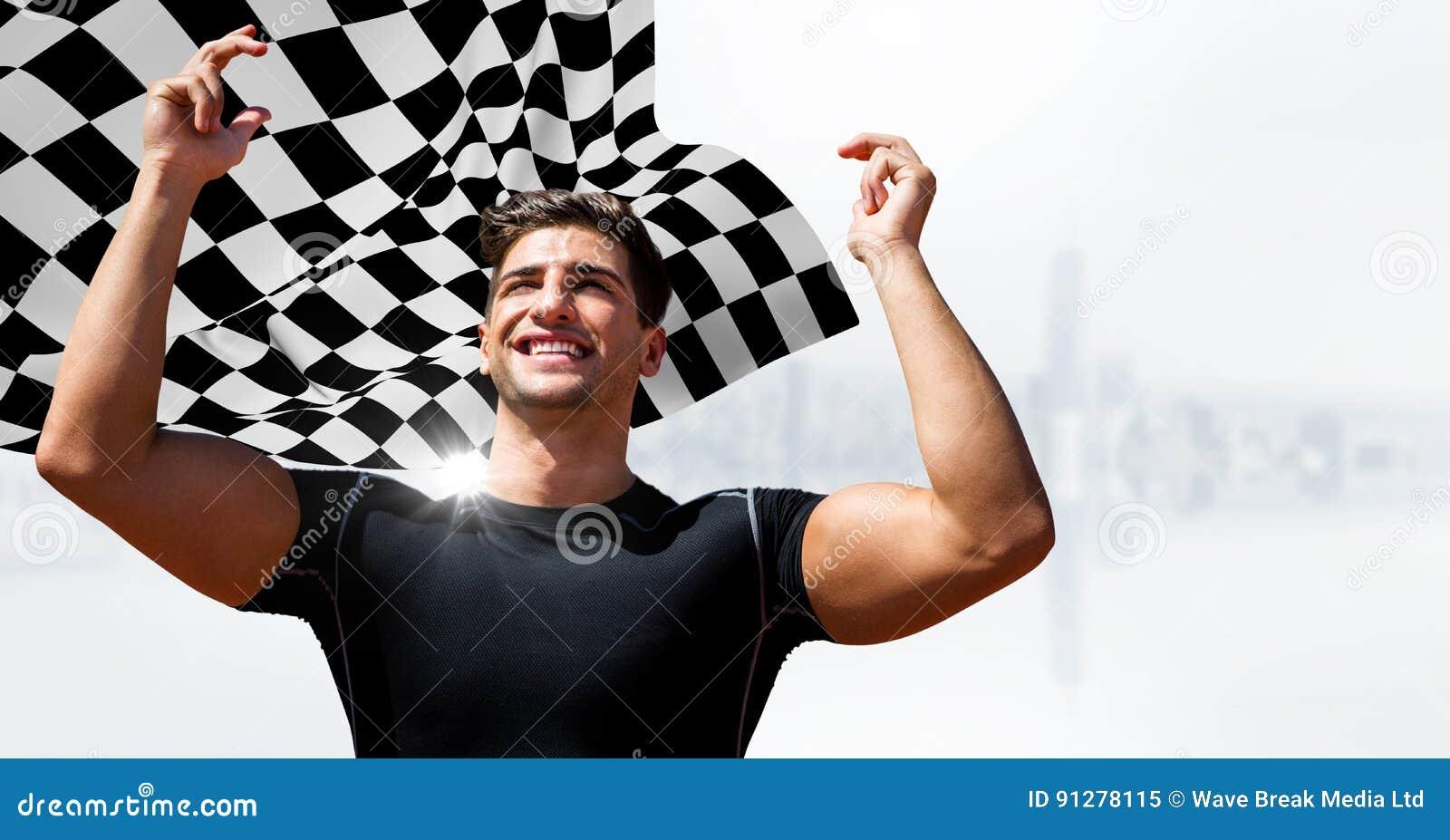 Manlig löpare med händer i luft mot vit horisont och rutig flagga