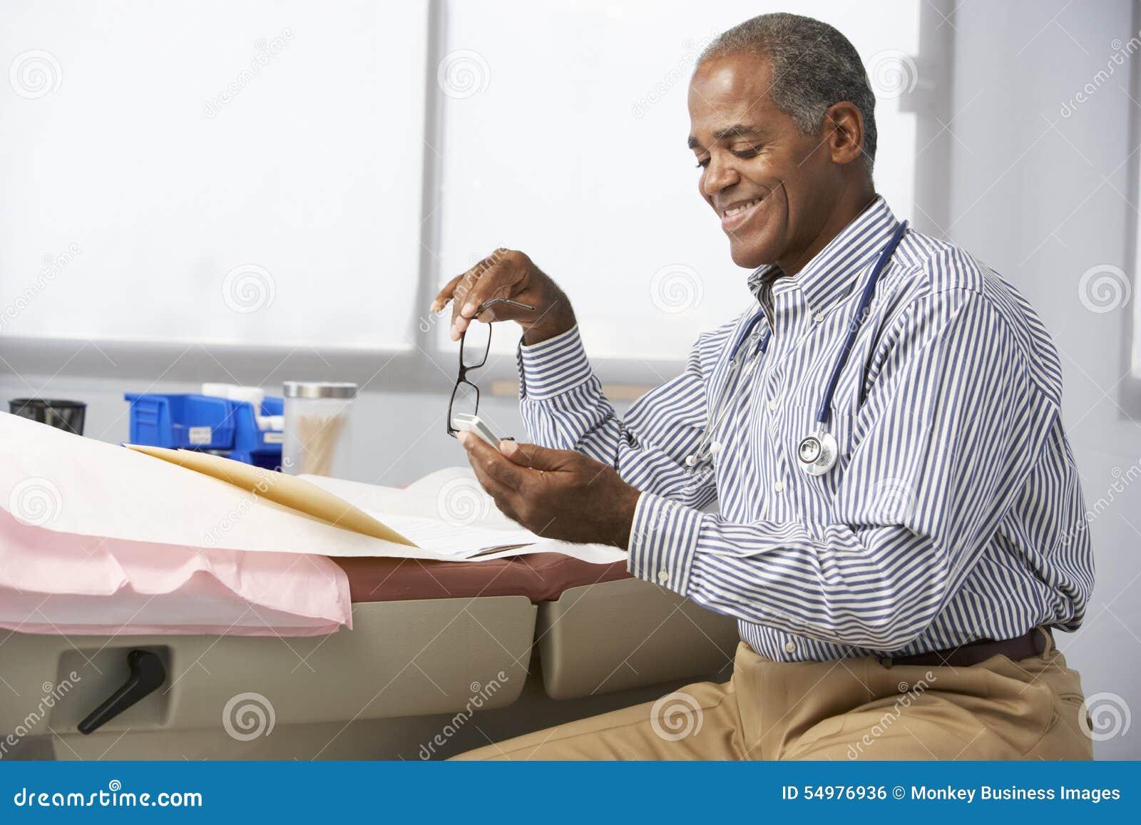 Manlig mobiltelefon för doktor In Surgery Using