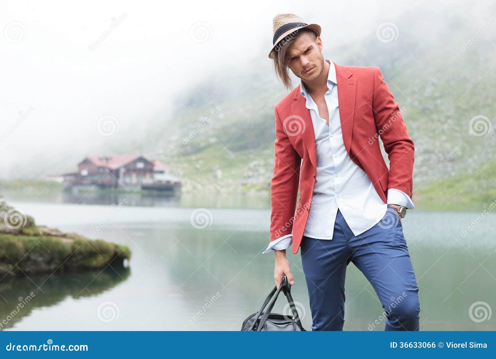 Manlig modell för mode som framme poserar av en sjö