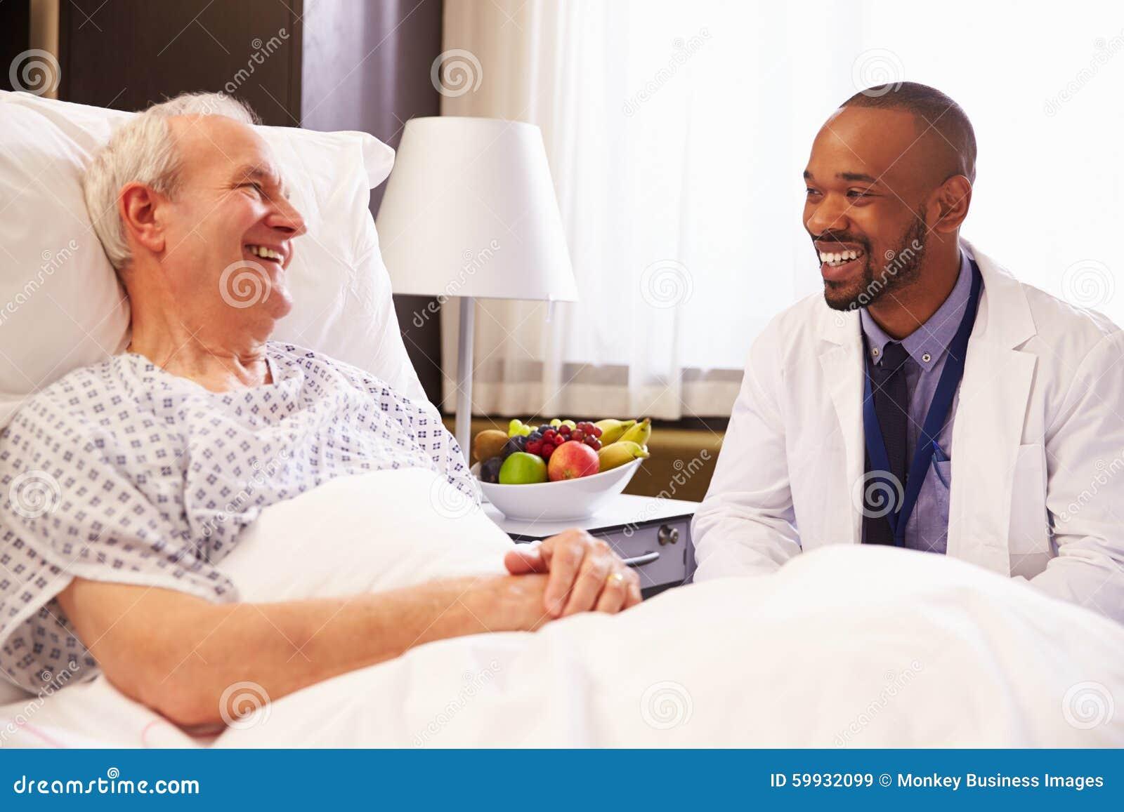 Manlig patient för doktor Talking To Senior i sjukhussäng