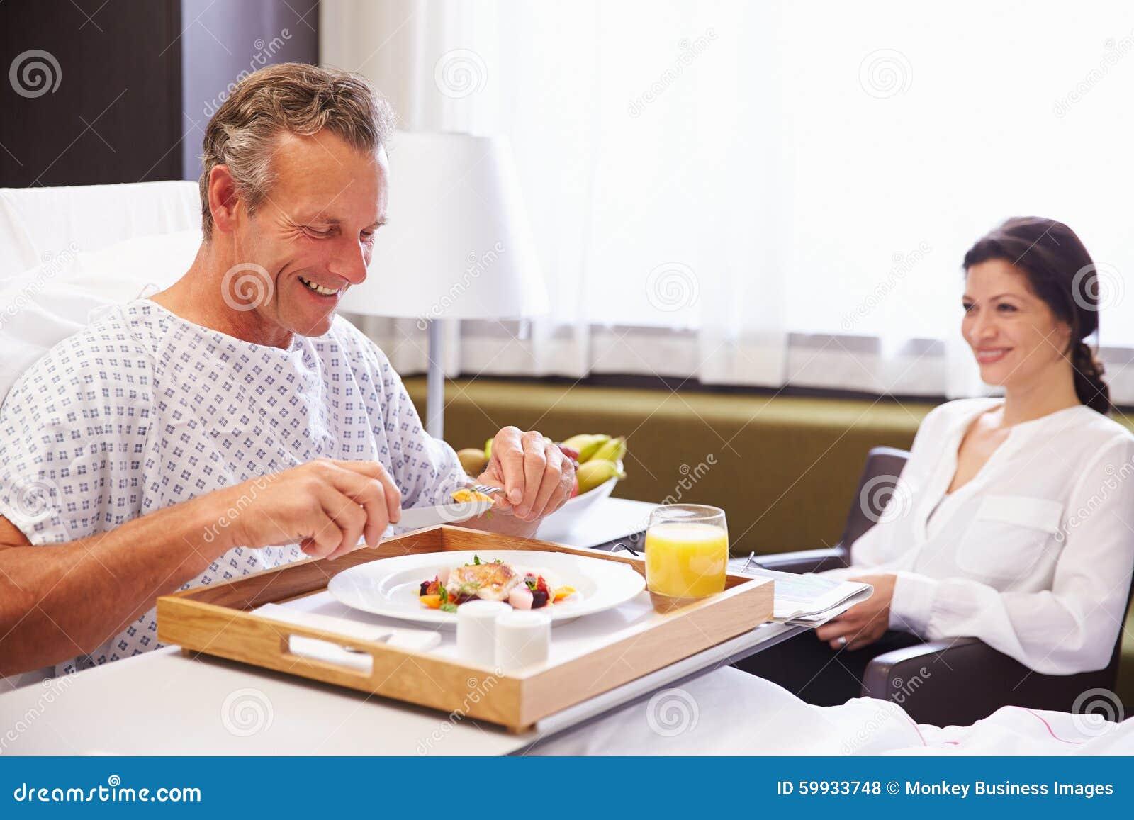 Manlig patient i sjukhussäng som äter mål från magasinet
