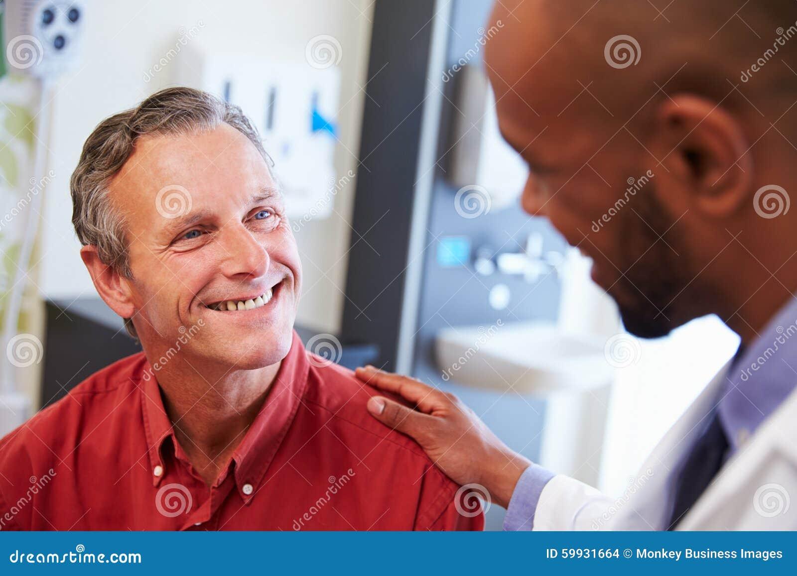 Manlig patient som uppmuntras av doktor In Hospital Room