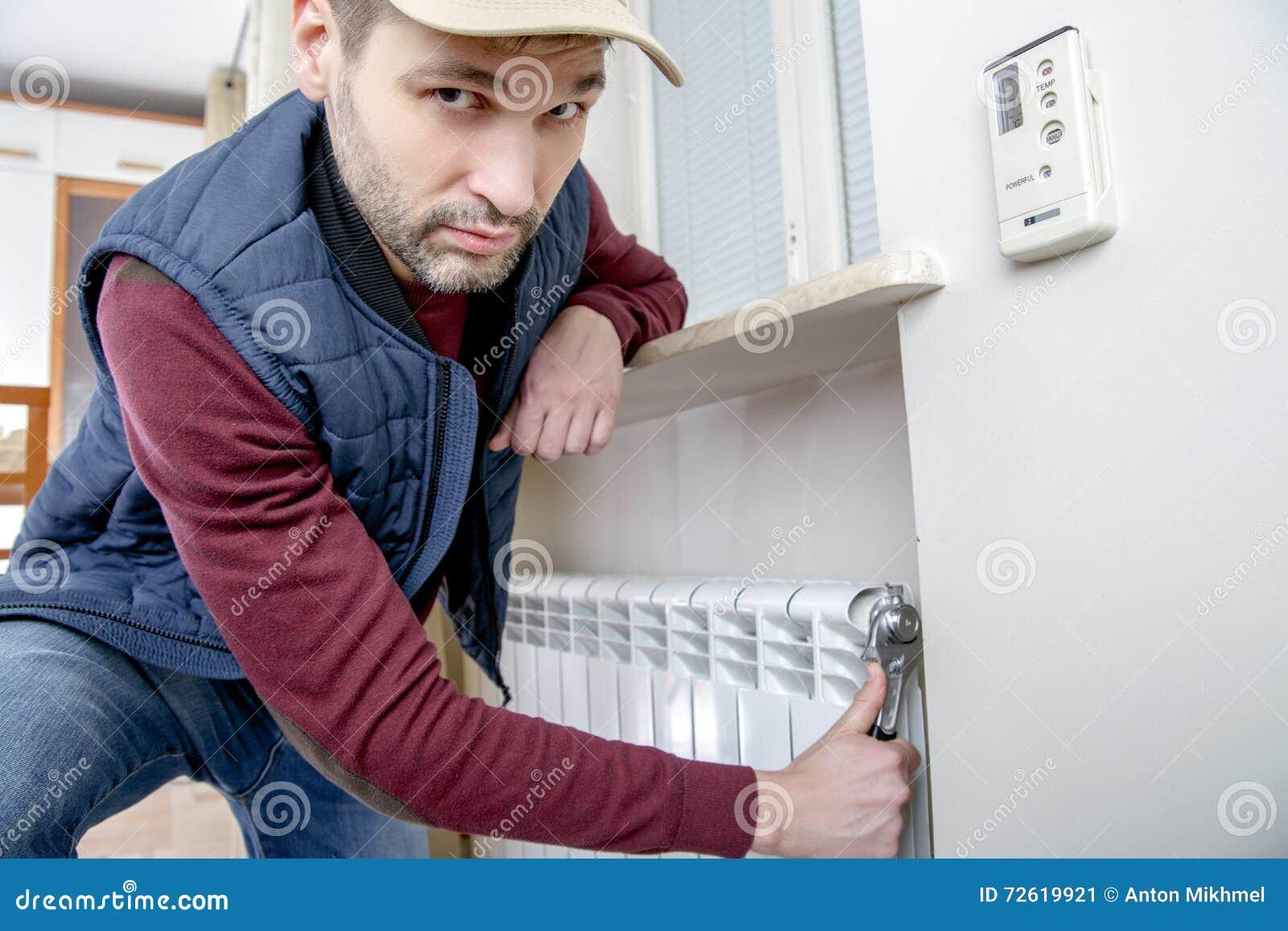Manlig rörmokare som reparerar elementet med skiftnyckeln