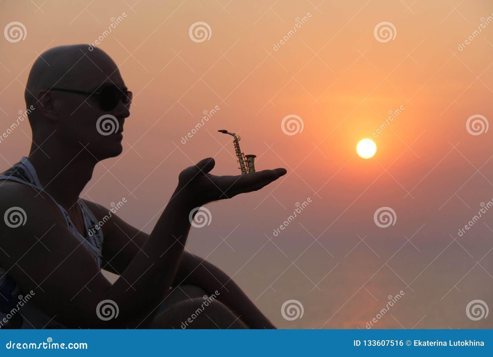 Manlig saxofonist på solnedgången Alt- saxofon på solnedgången silhouette