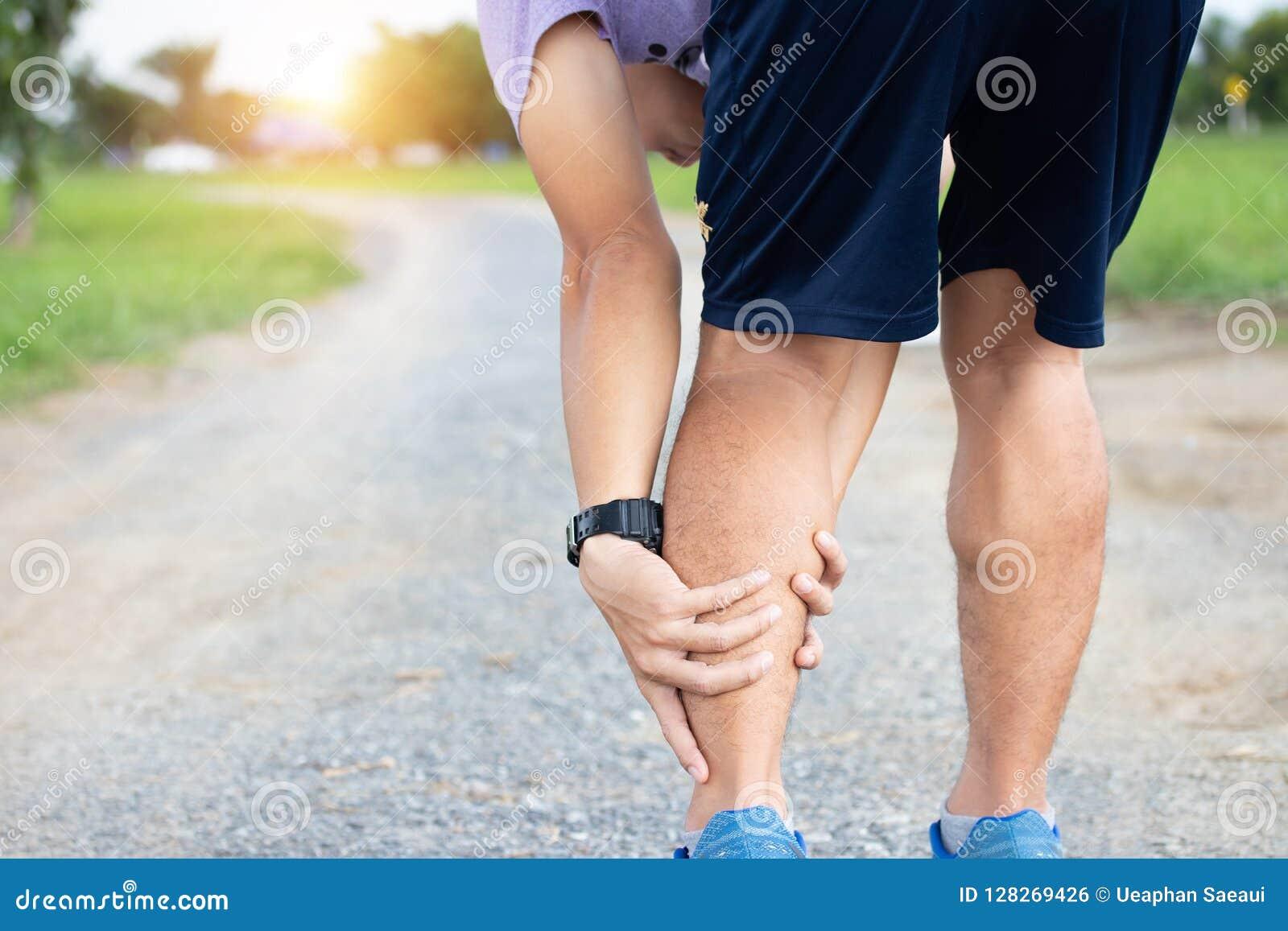 Manlig skada för för idrottsman nenlöparemuskel och ankel, når att ha joggat Athle