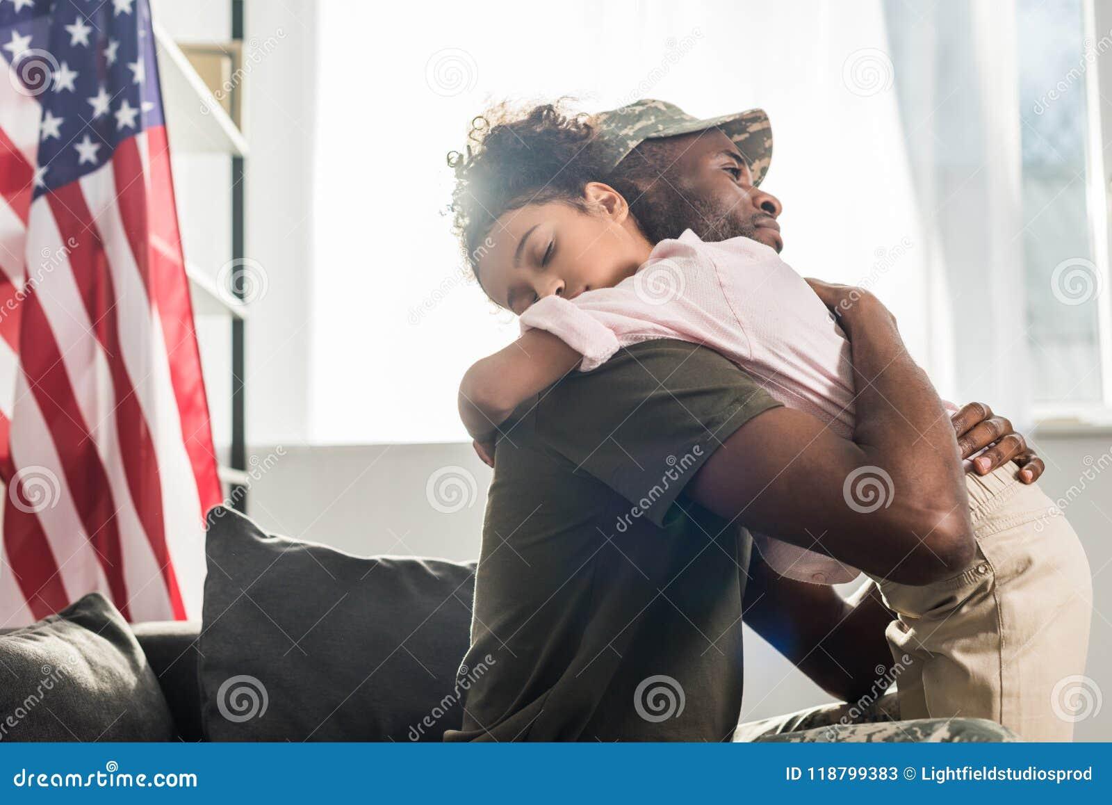 Manlig soldat i kamouflagekläder och hennes omfamna för dotter