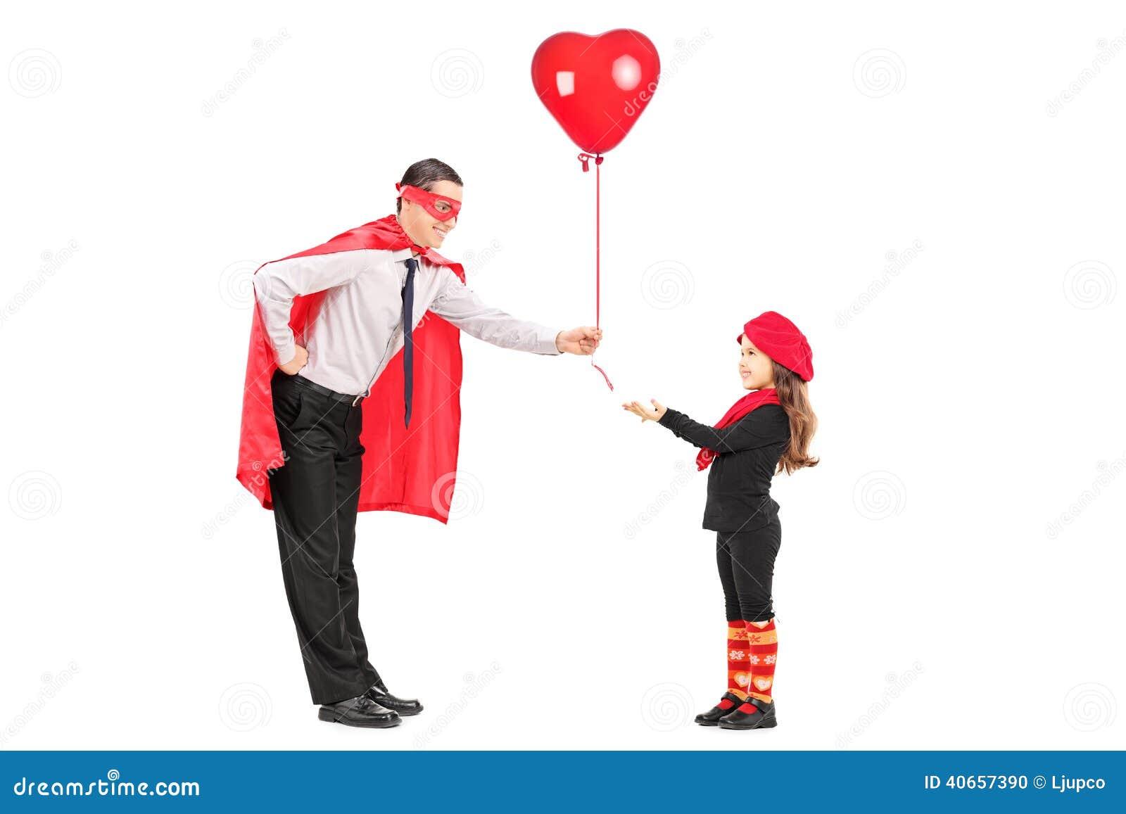 Manlig superhero som lite ger en ballong till flickan