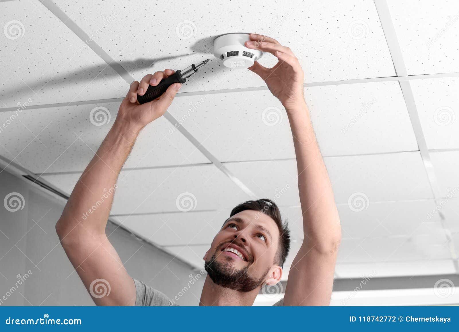 Manlig tekniker som inomhus installerar röklarmsystemet