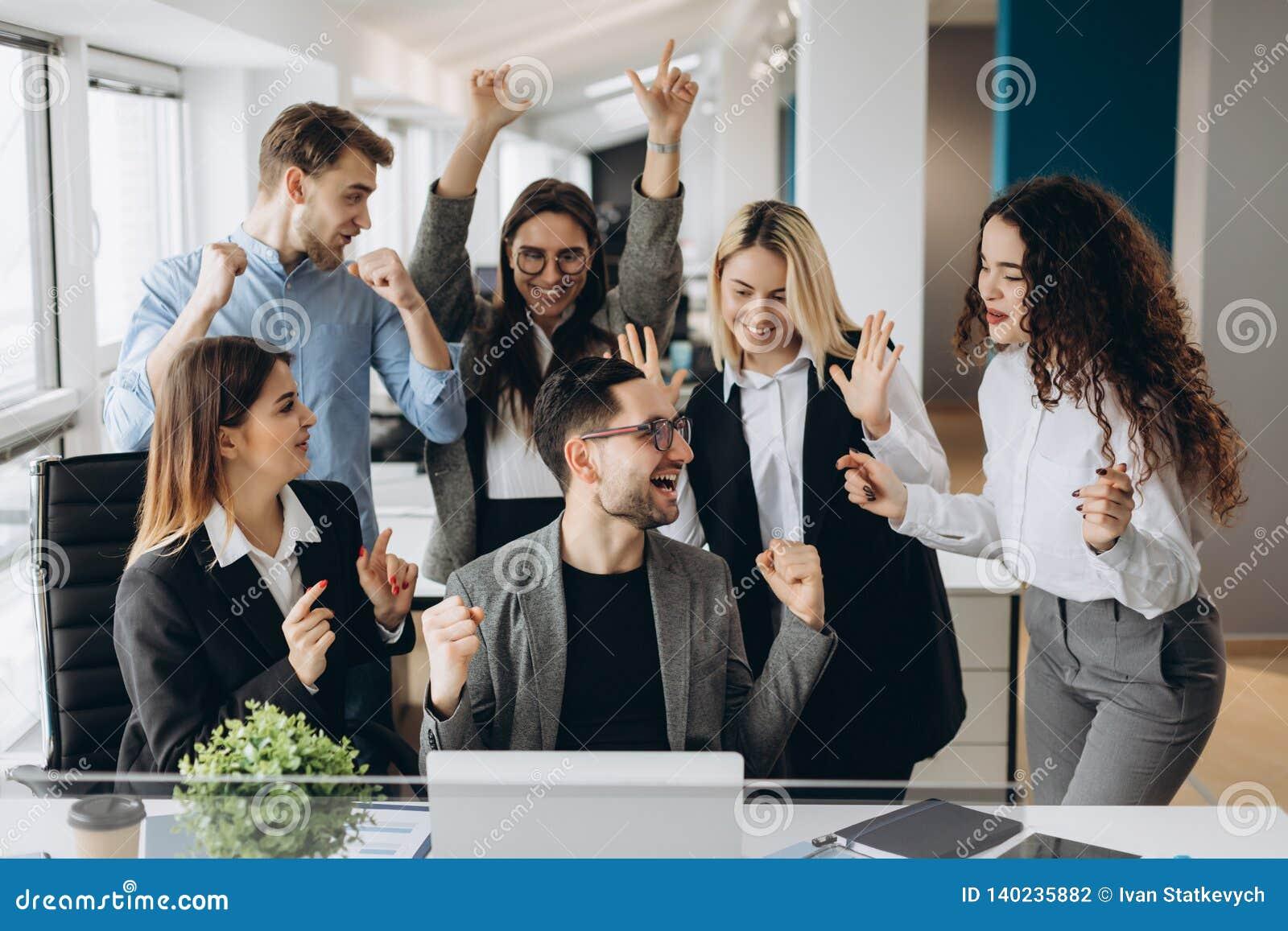 Manliga arbetaraktiegoda nyheter med blandras- kollegor i delad arbetsplats, olika anställda skriker med lycka spännande med