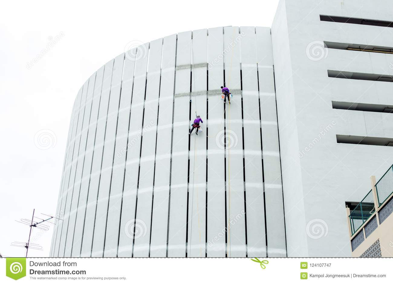 Manliga byggnadsarbetare i yrkesmässiga målninghjälpmedel för overaller Byggnadsreparationer på yttre väggar