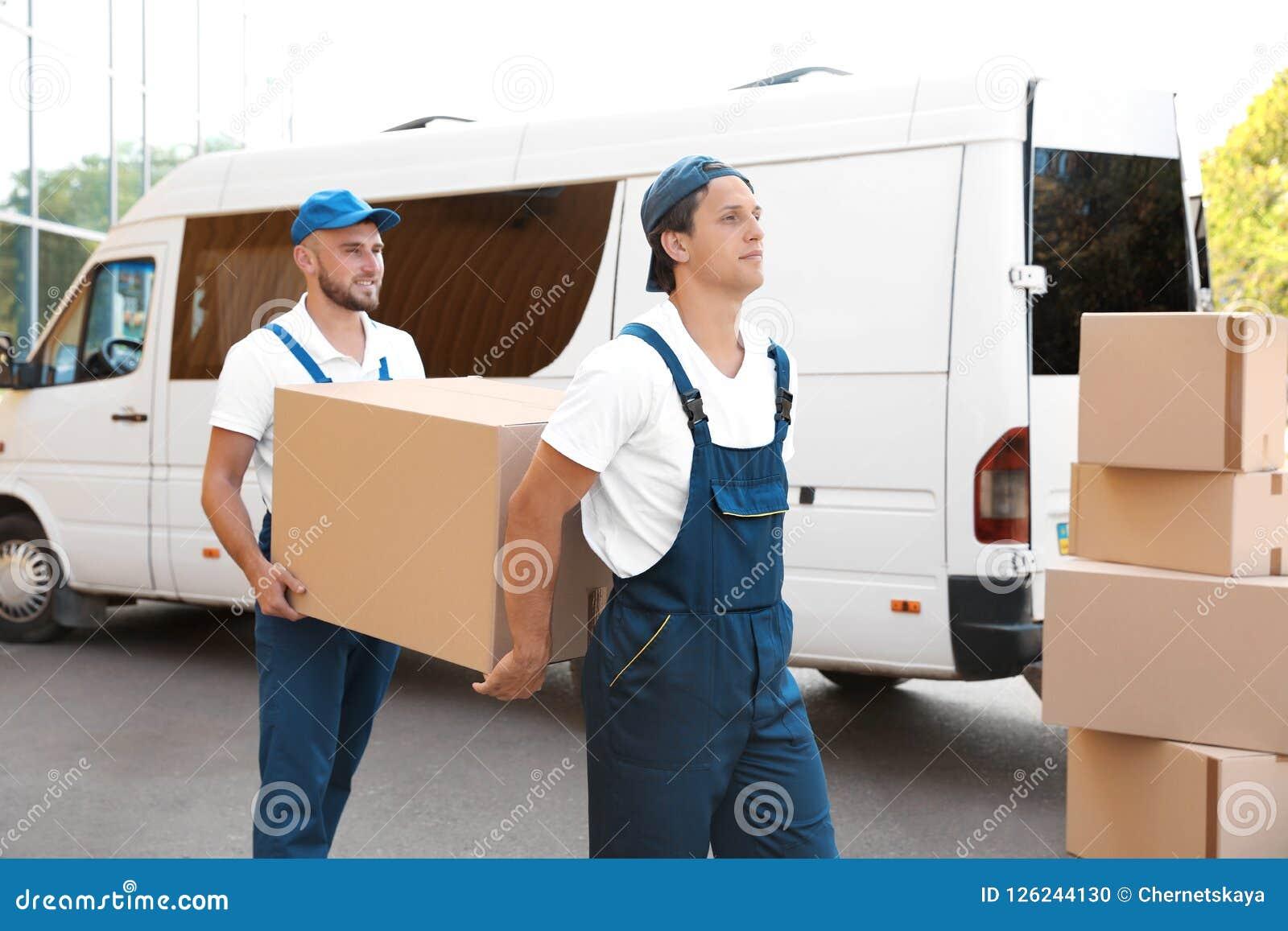 Manliga flyttkarlar som lastar av askar från skåpbilen