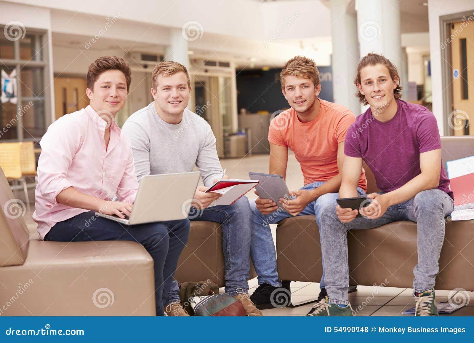 Manliga högskolestudenter som tillsammans sitter och talar