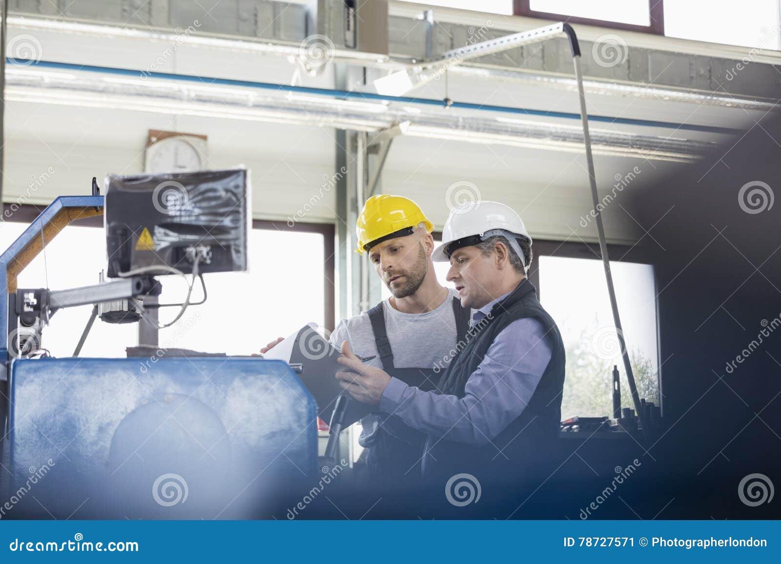 Manliga manuella arbetare som fungerar maskineri på metallbransch