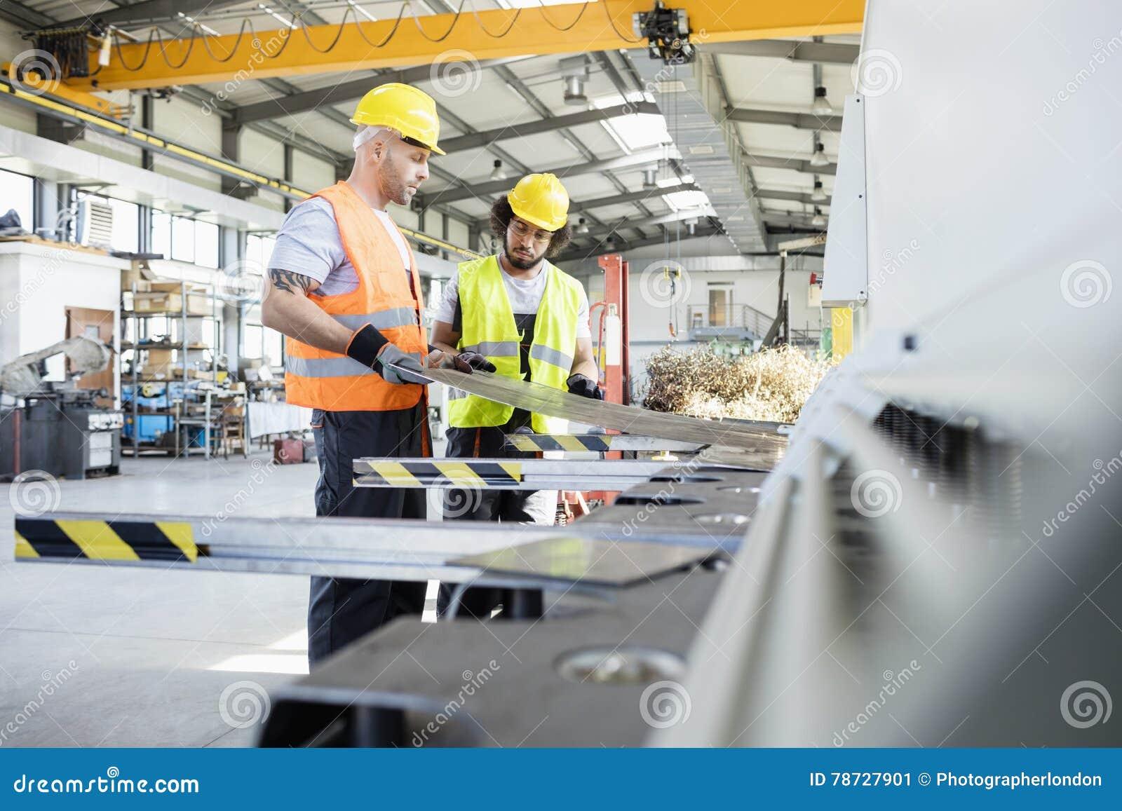 Manliga manuella arbetare som undersöker arkmetall på bransch