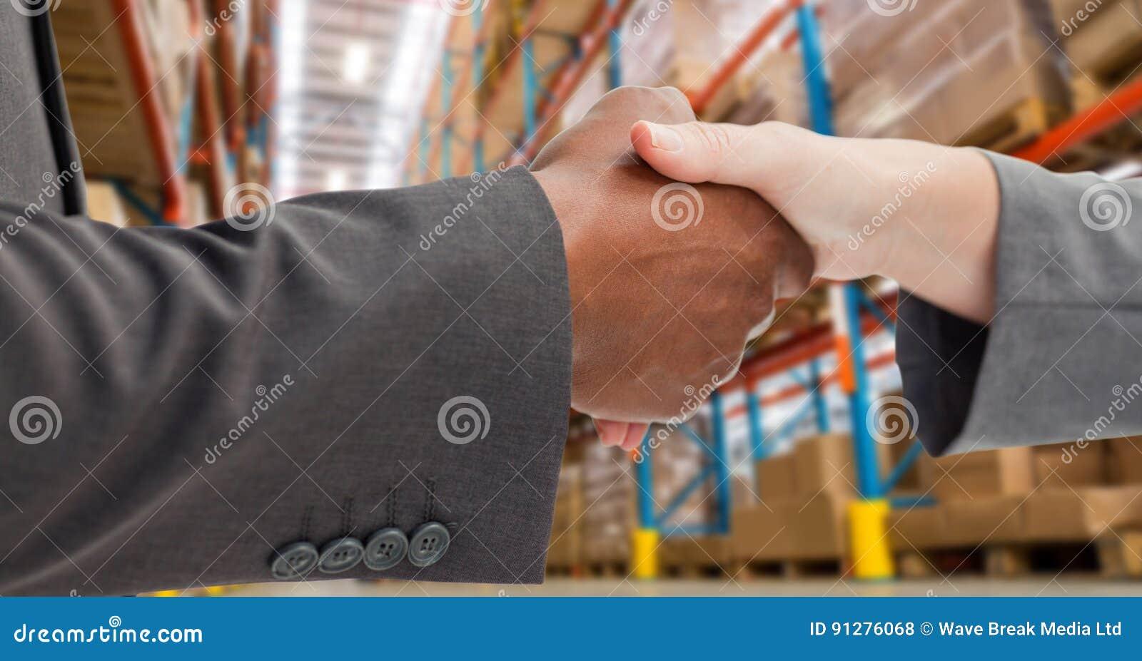 Manliga och kvinnliga affärspartners som skakar händer i lager
