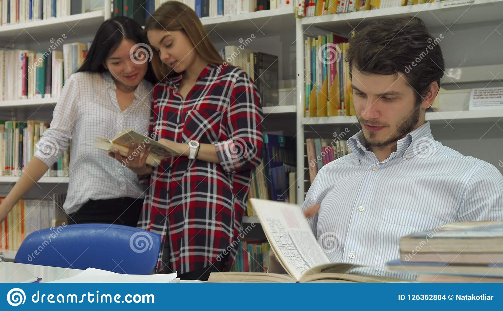 Manliga studenter läser boken på arkivet