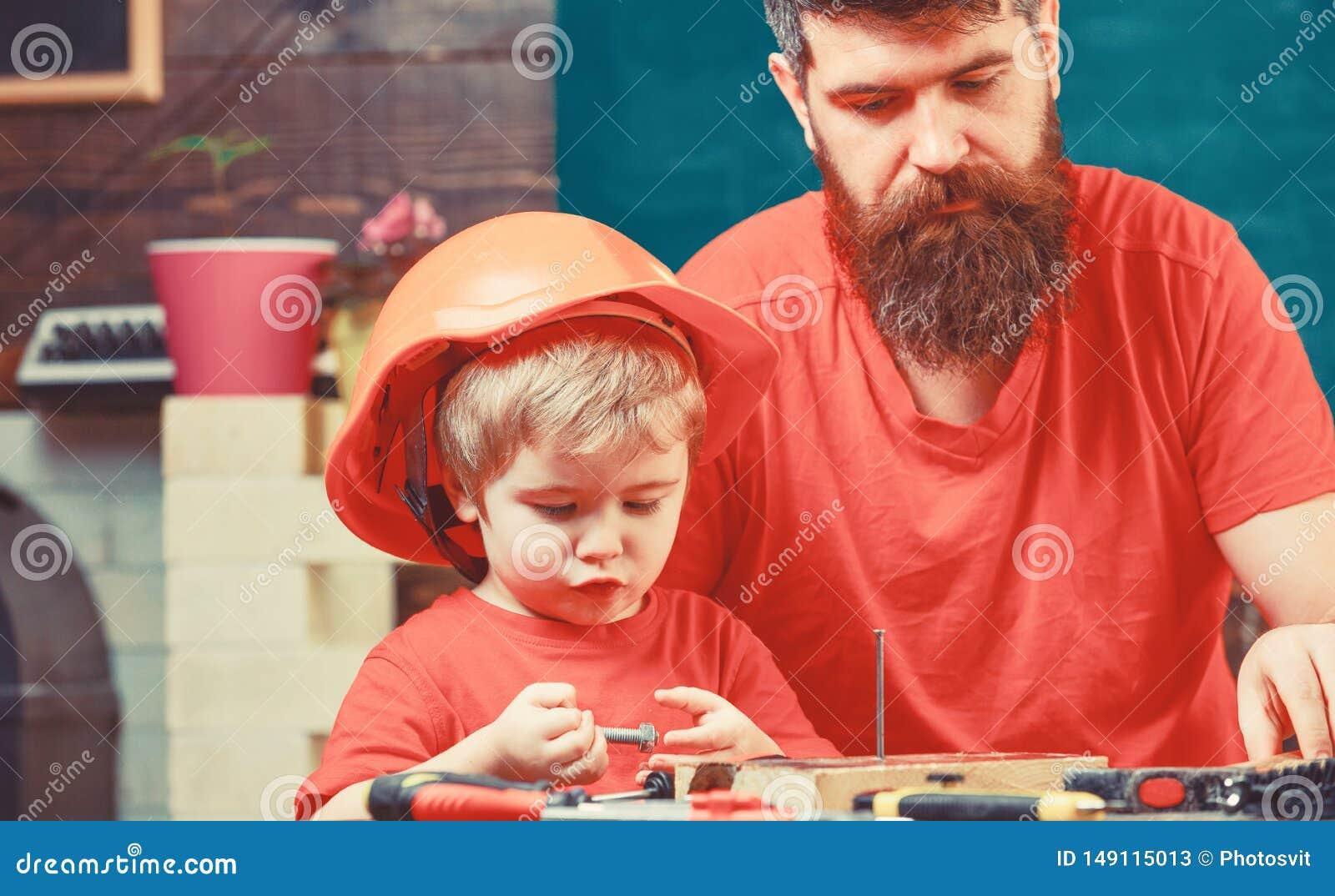 Manligt arbetsuppgiftbegrepp Pojke barn som ?r upptaget i skyddande hj?lm som l?r till att bulta grovt sulstift med farsan Fader