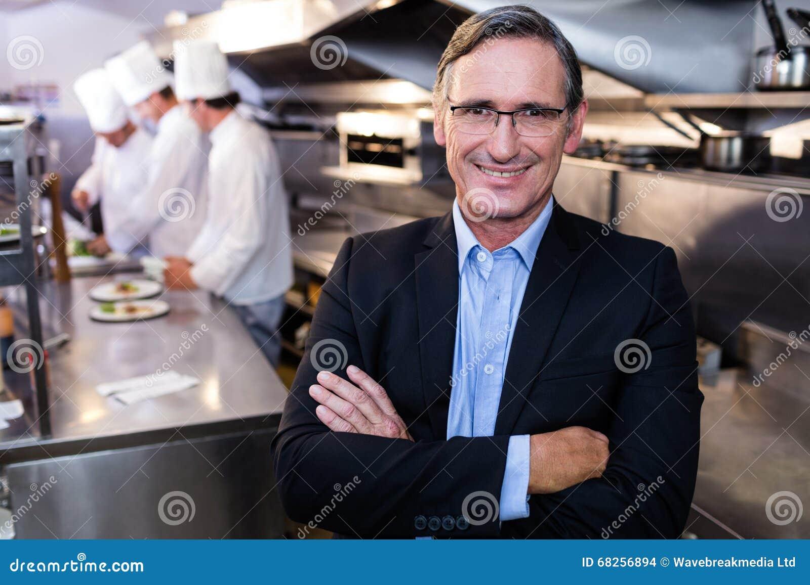 Manligt restaurangchefanseende med korsade armar