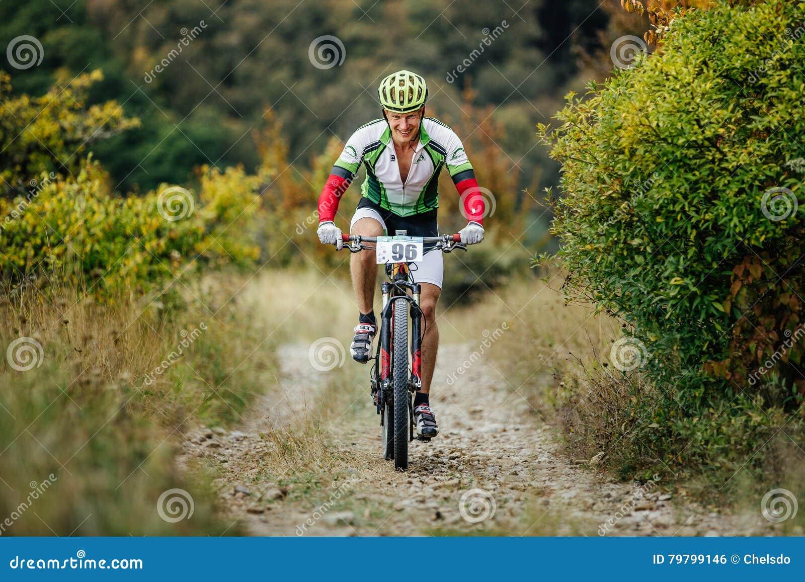 Manligt rida för ryttarecyklist som är stigande på en bergslinga med leende på framsida