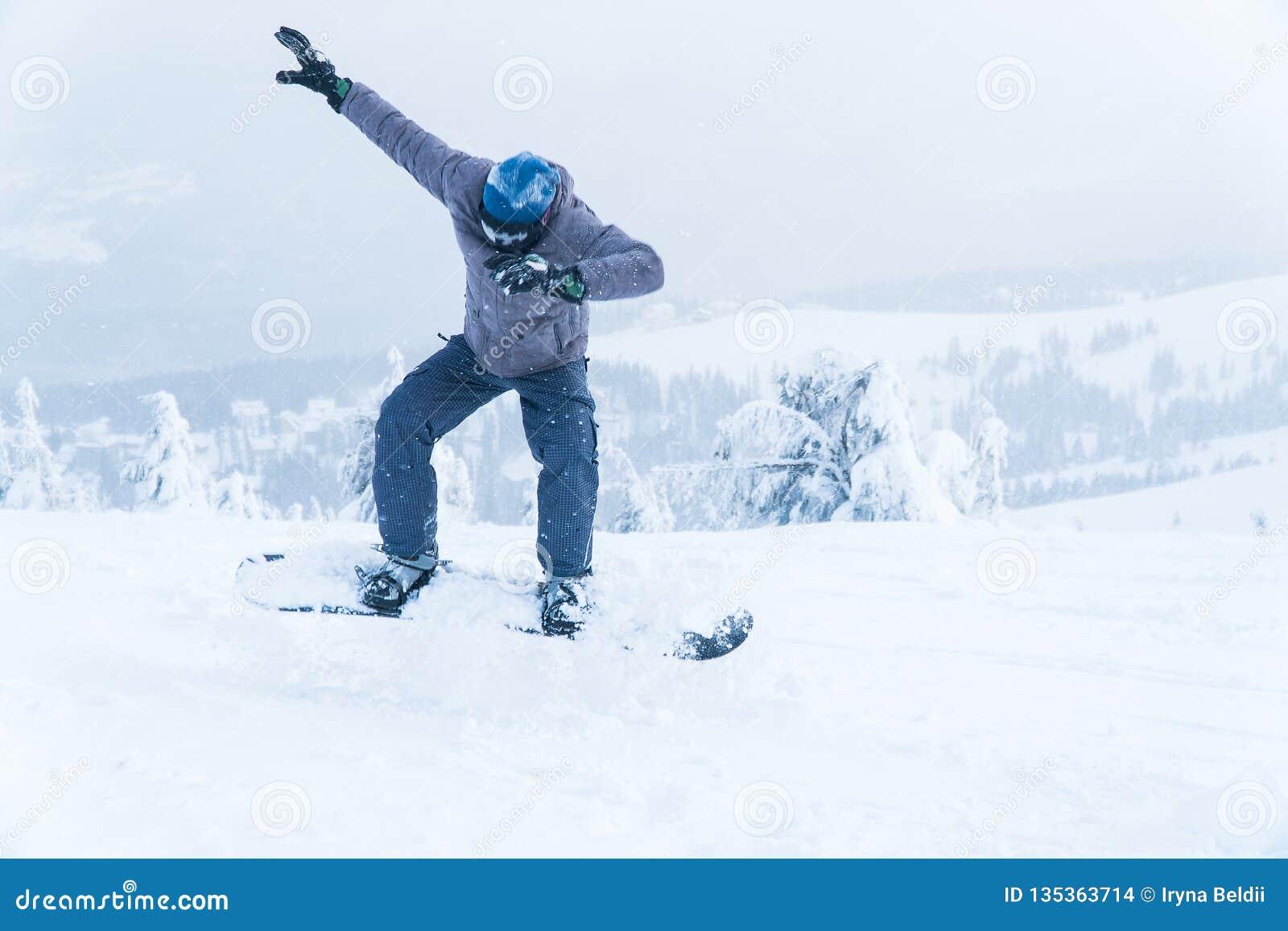 Manligt snowboardingsnowboardhopp gå i bergen på snowboarding för snöbergvinter